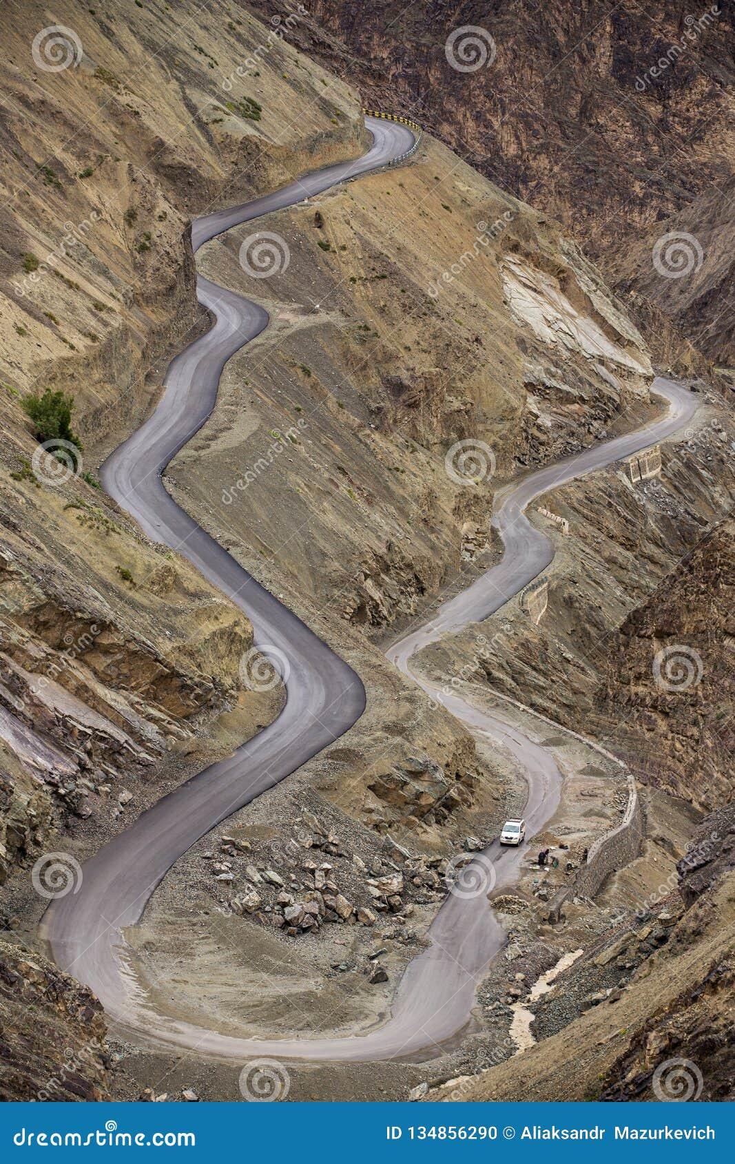 Curva afiada na estrada em montanhas de Himalaya, região da montanha de Ladakh