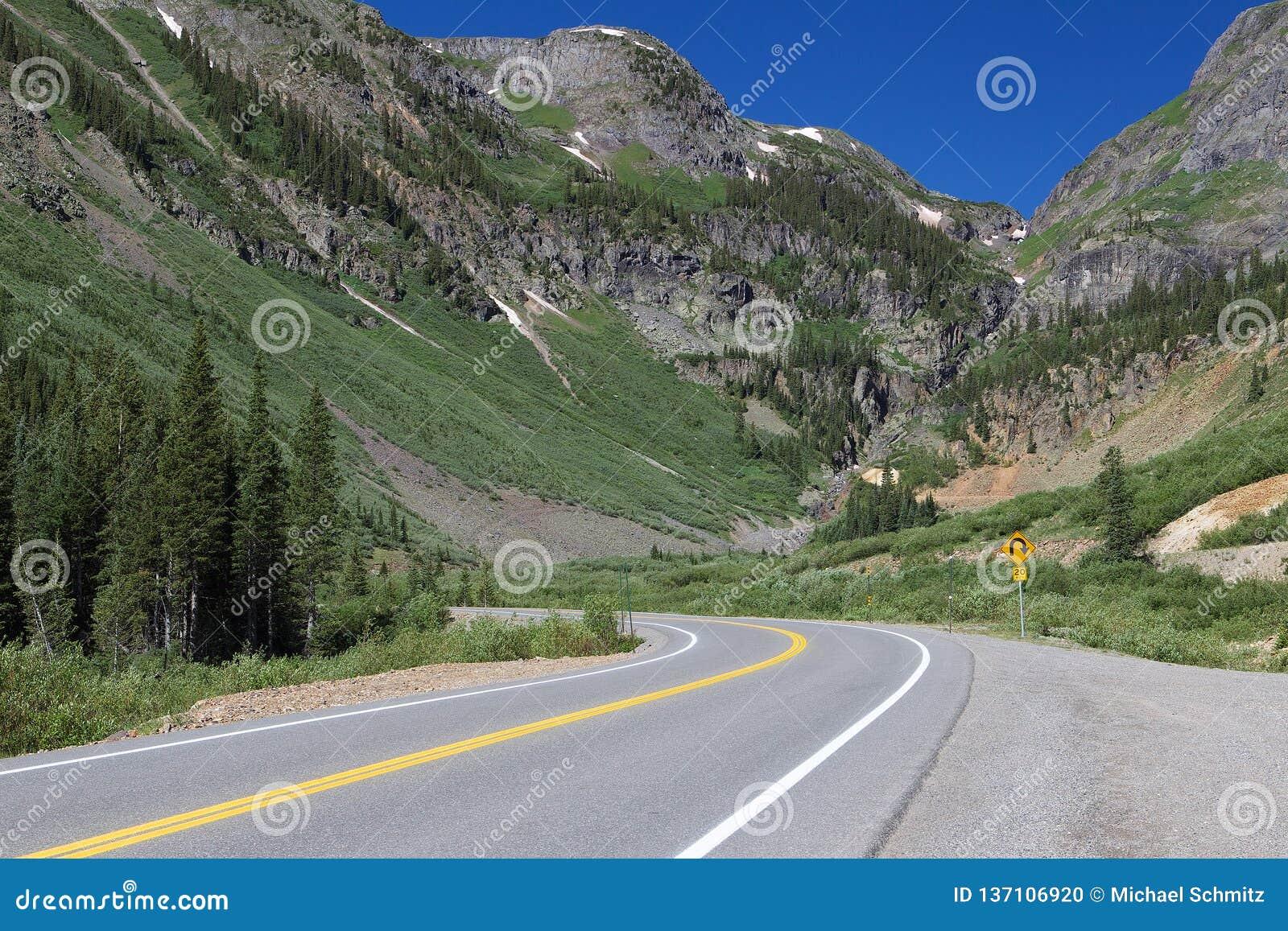 Curvas del camino de la montaña delante de las montañas grandes en Colorado