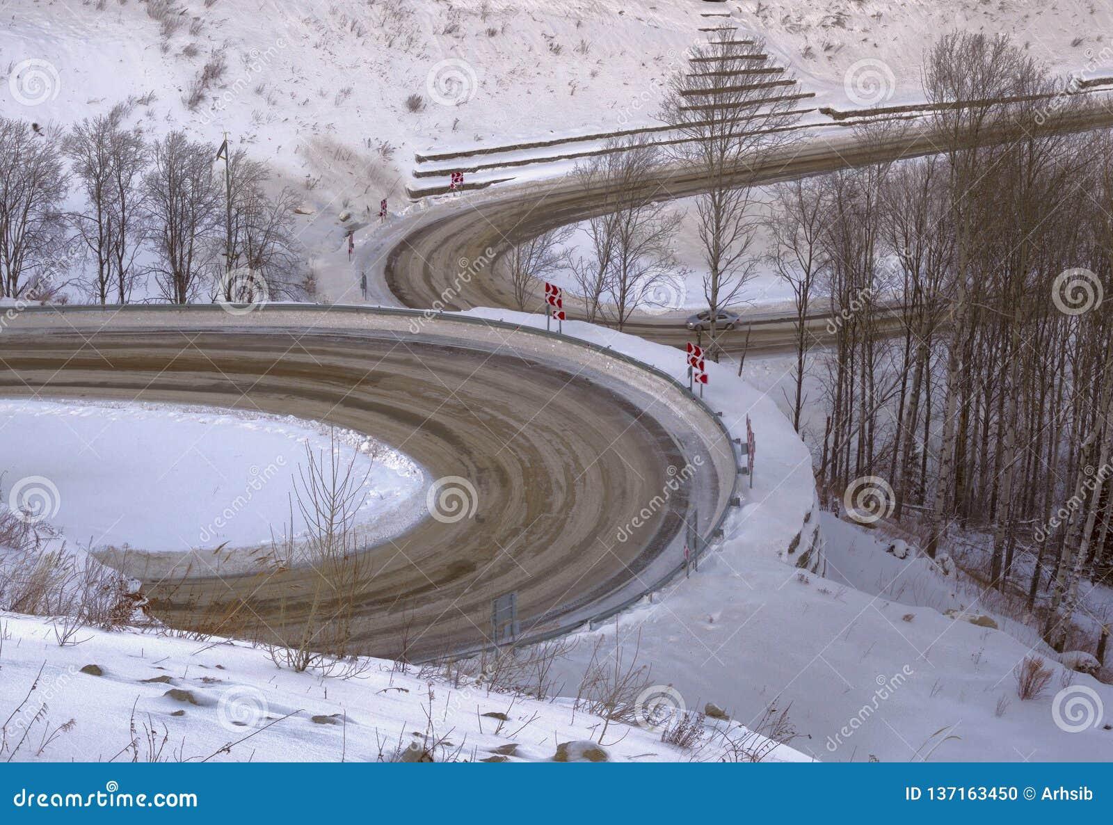 Curvaturas divergentes da estrada na paisagem do inverno