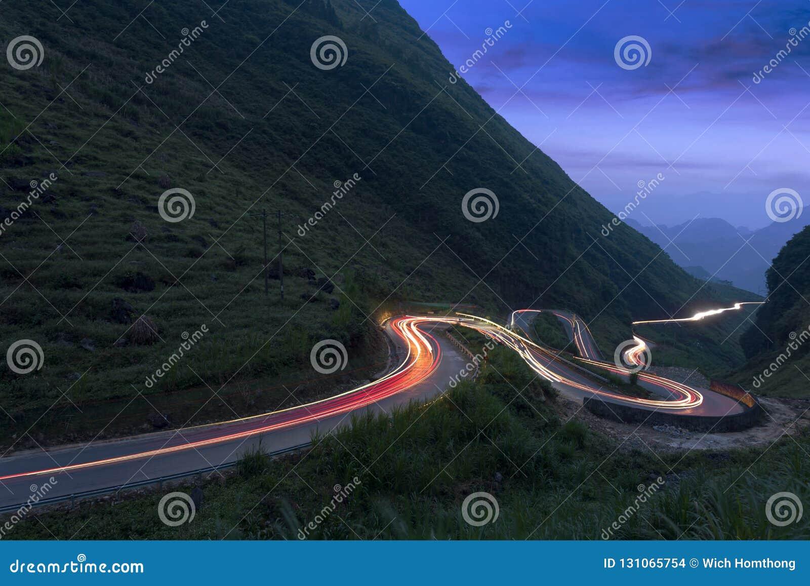 A curvy road through the grassy hills at twilight.