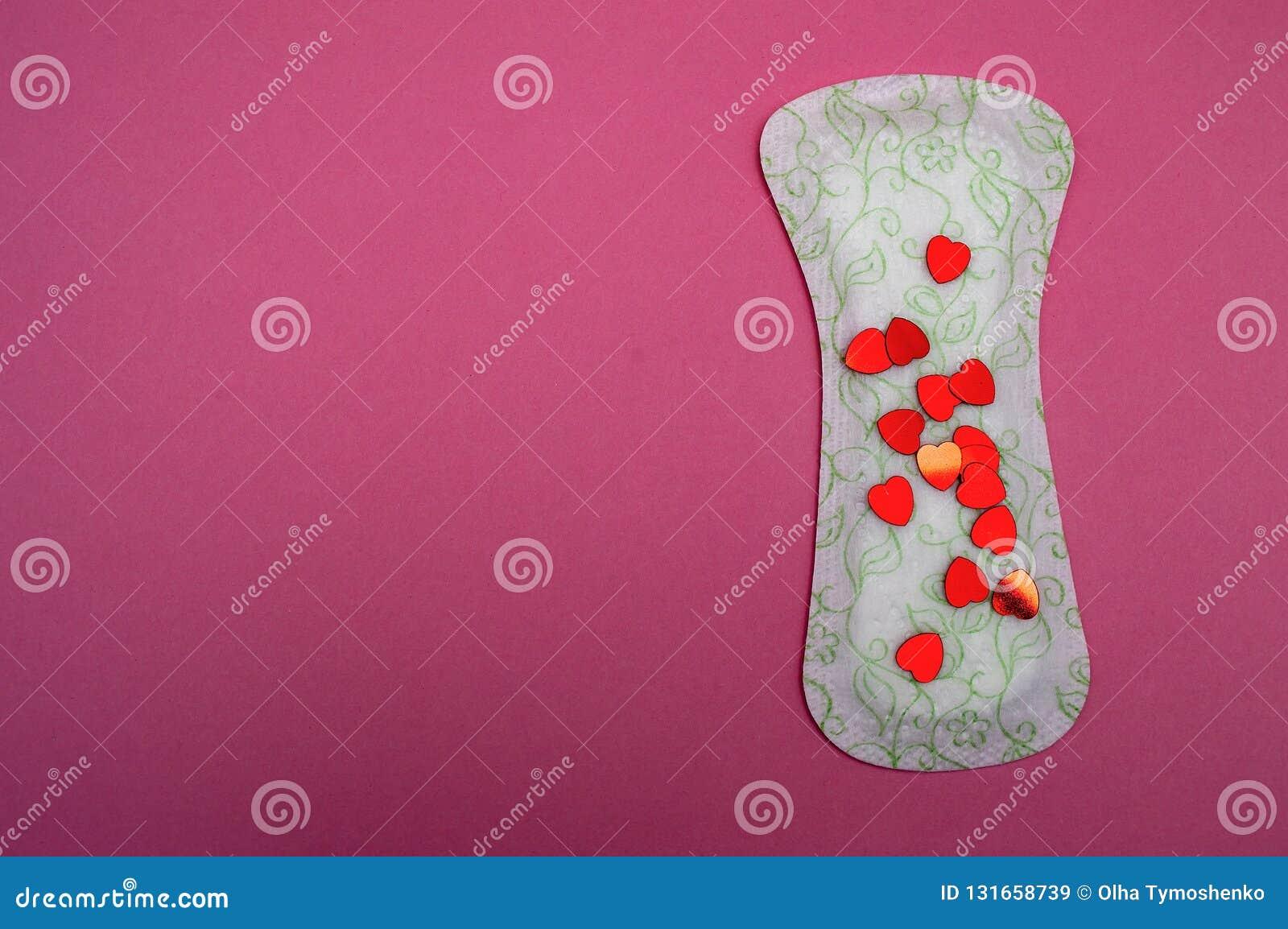Cuscinetto mestruale con uno scintillio rosso su fondo rosa il cotone esile