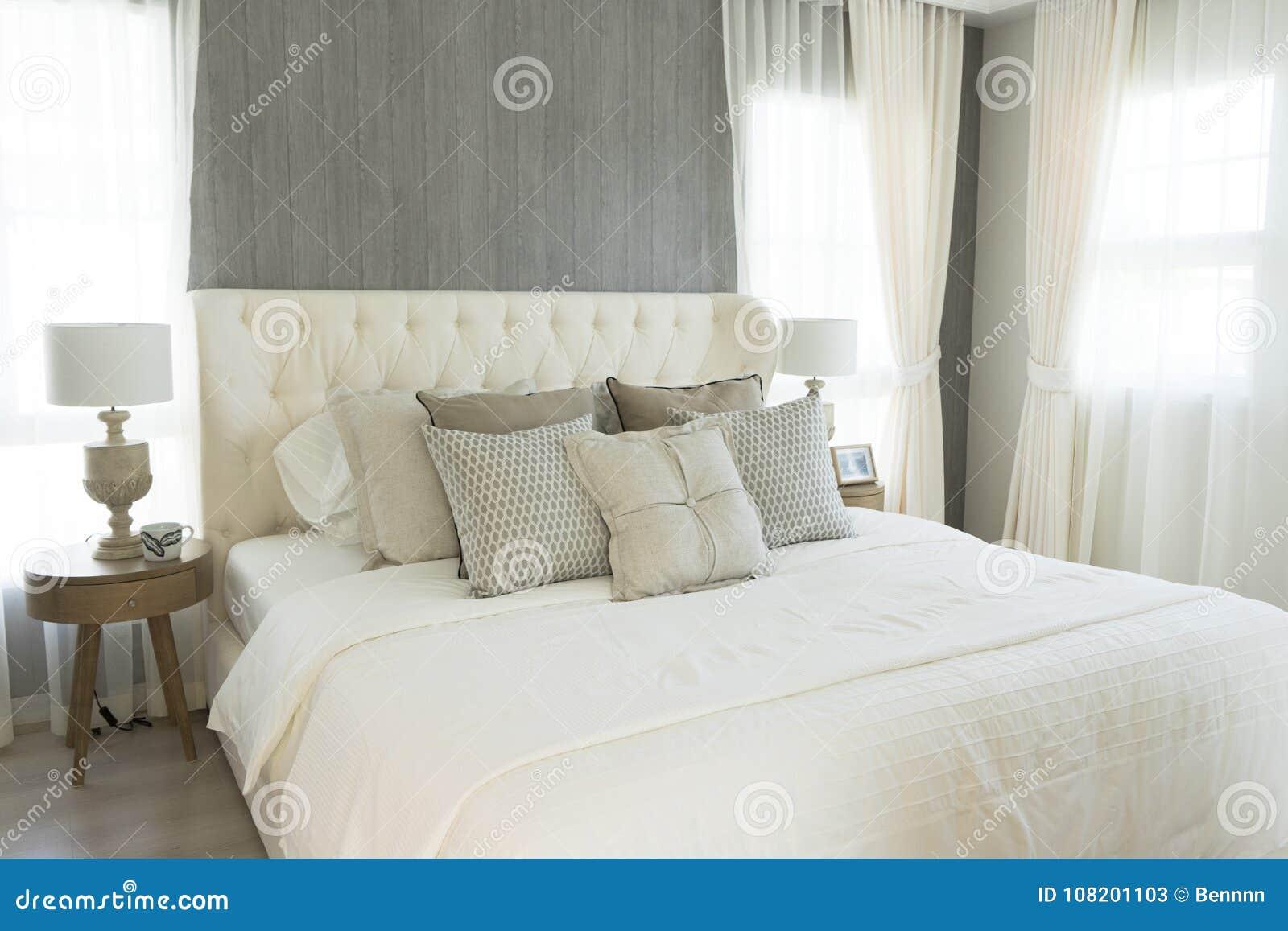 Cuscini bianchi che mettono sulla camera da letto stile country