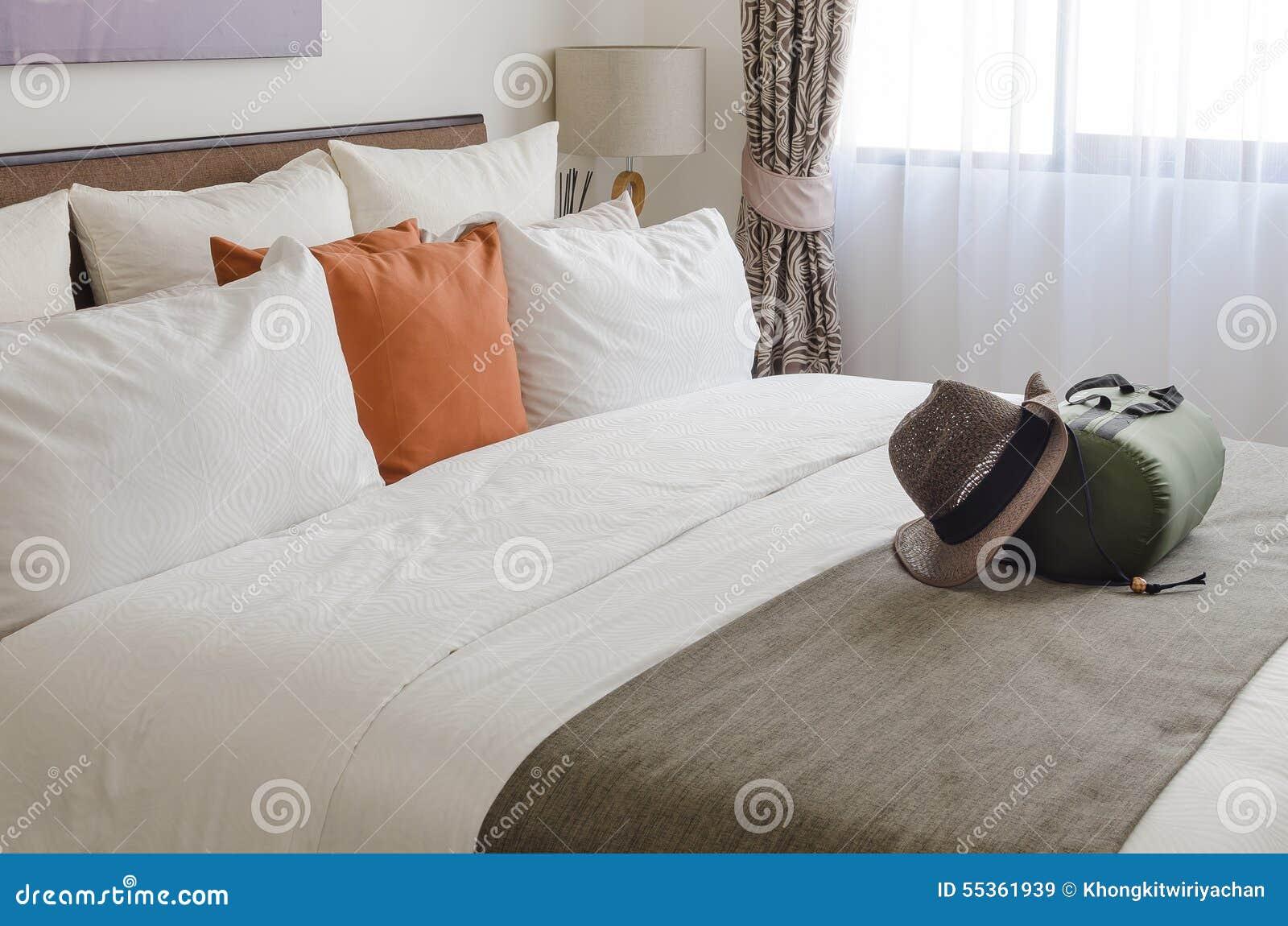 Cuscini sul letto in salone moderno con il cappello e la borsa di viaggio