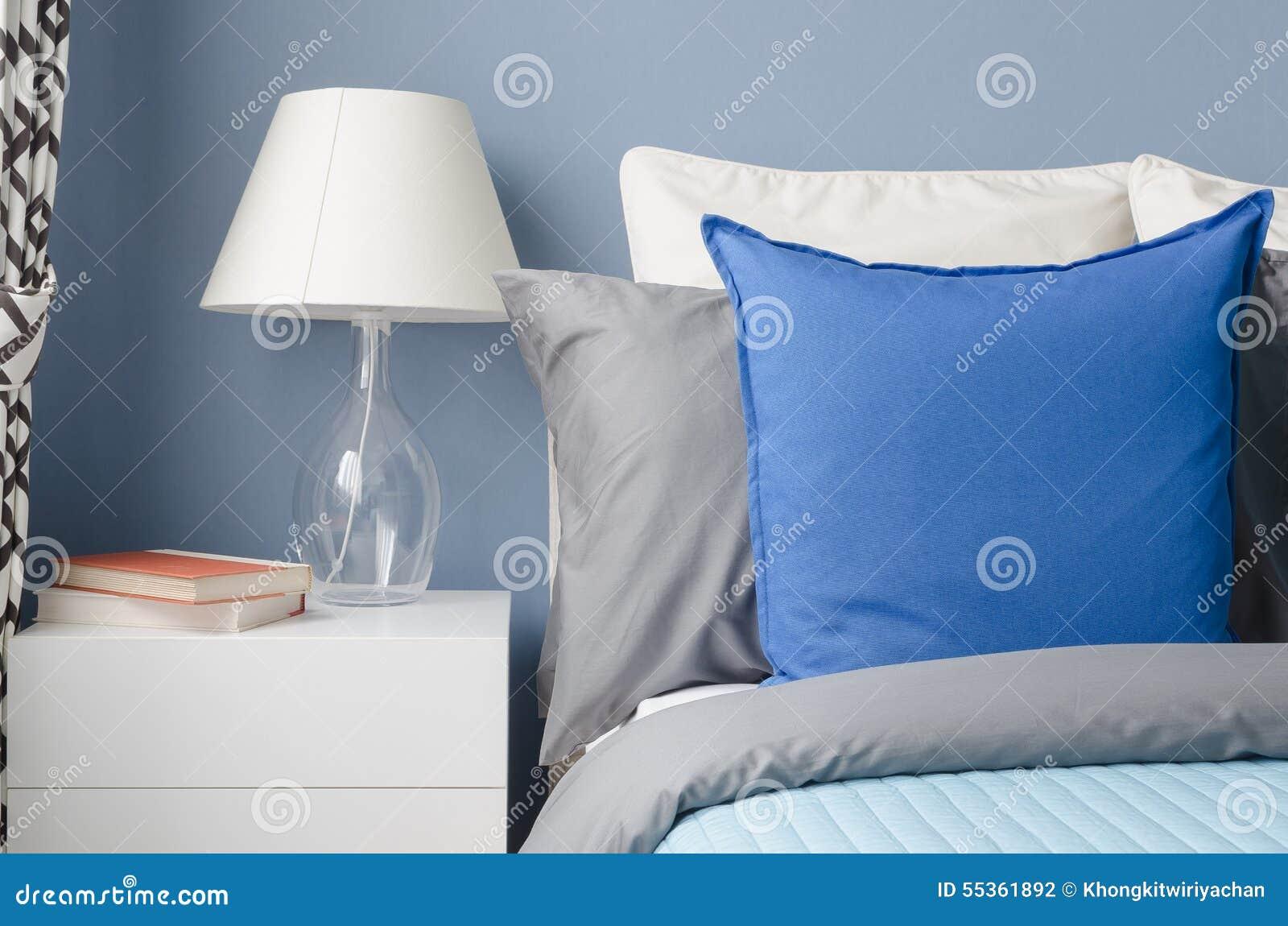 Cuscino blu sul letto con la lampada di vetro sulla tavola bianca in blu moderno