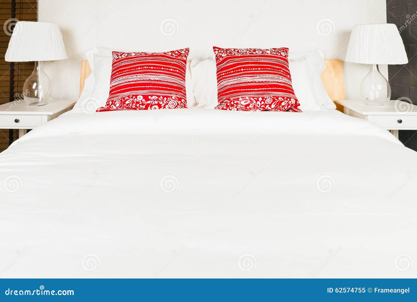 Camere Da Letto Rosse E Bianche : Cuscino rosso sulla camera da letto con il lenzuolo e la lampada