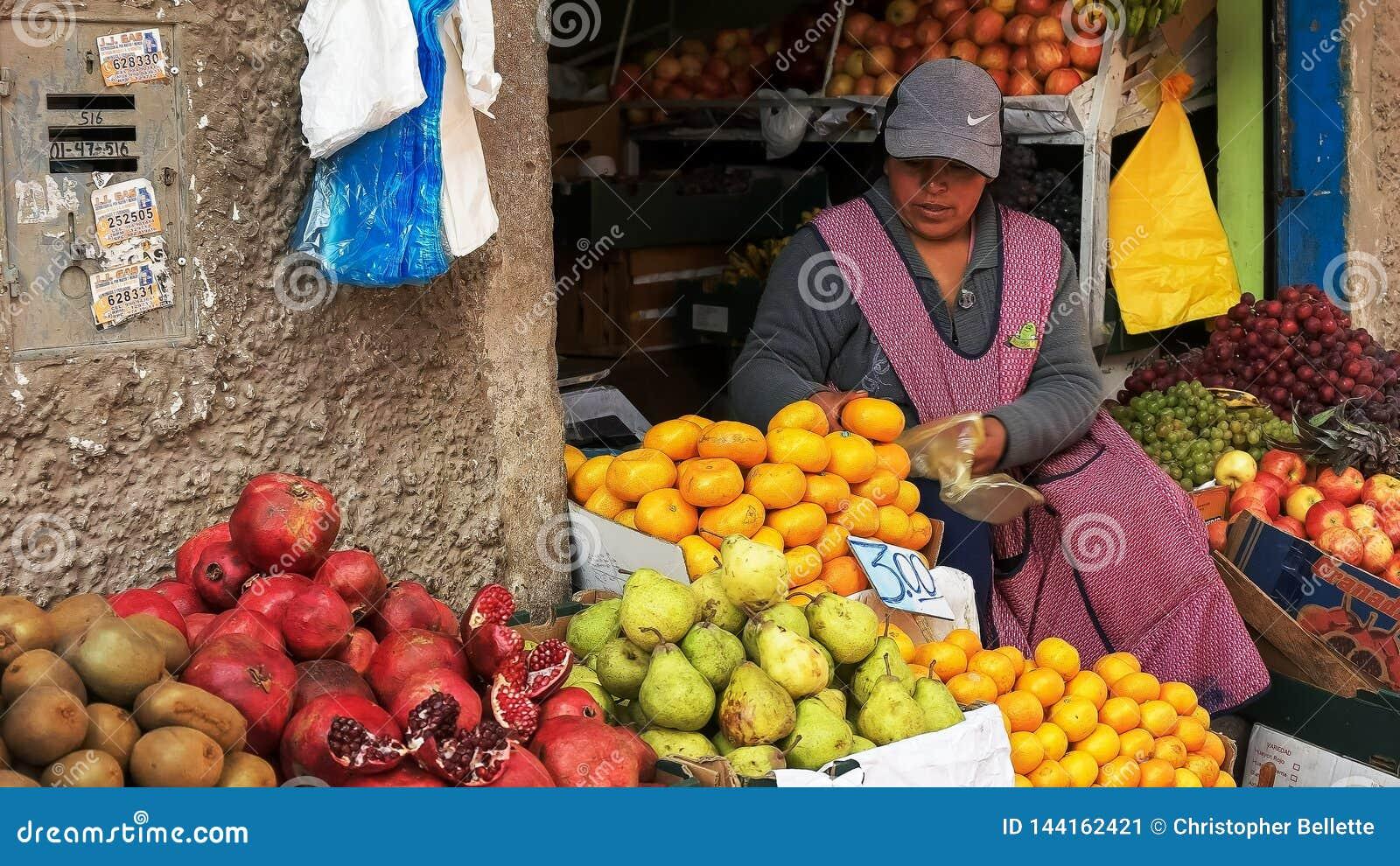 CUSCO, PERU 20. JUNI 2016: eine Frau sackt frische Mandarinen an einem Markt im cuzco ein