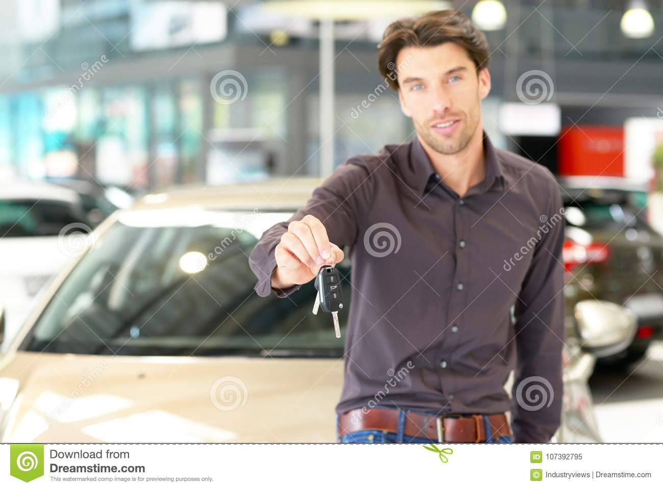 Customer in the car dealership holds the car key of the newly pu