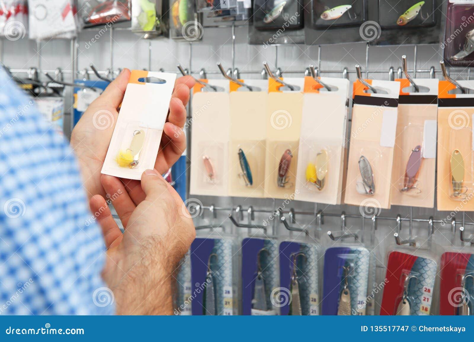 Customer choosing fishing equipment in sports shop, closeup.