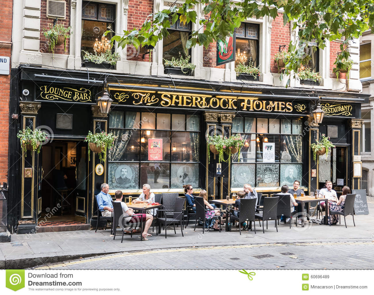 Customers Drink Beer At Tables Outside Sherlock Holmes Bar In London