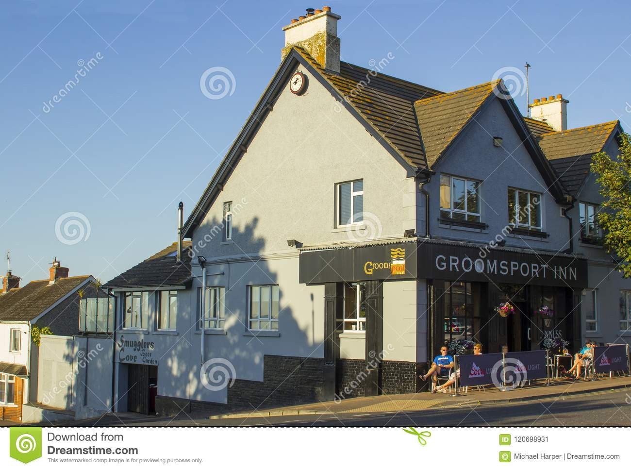Customers drinking at a table outside the village pub at Groomsport in County Down Northern Ireland