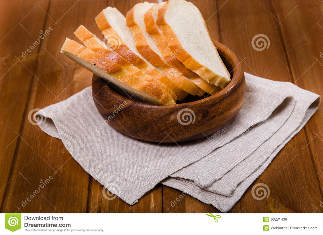 The cut bread costs on a linen napkin in a wooden bowl