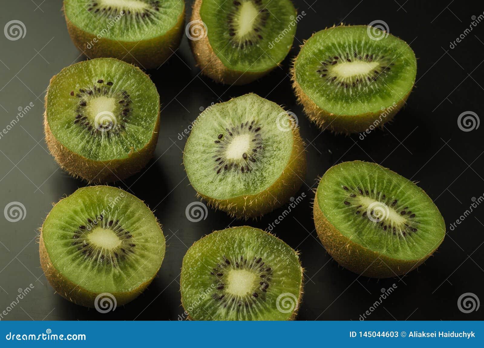 cut kiwi against black background/cut kiwi against black background. Top view