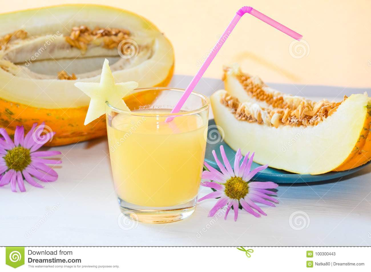 Cut melon in half next pieces of melon on a plate glass of smoothie with a straw of melon and autumn flowers asters