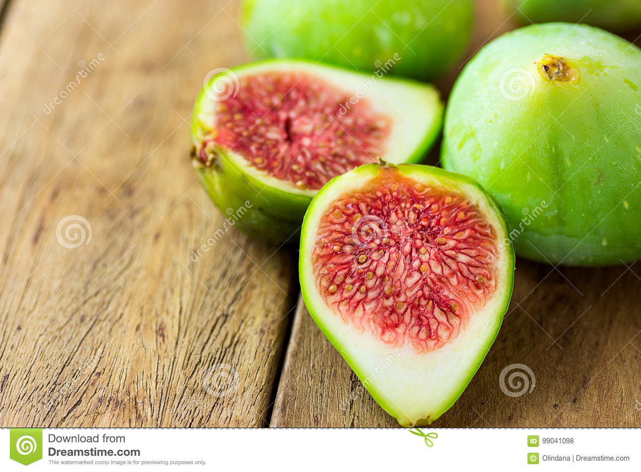 Cut open halved ripe green fig with red pulp. Aged plank wood background. Copy space