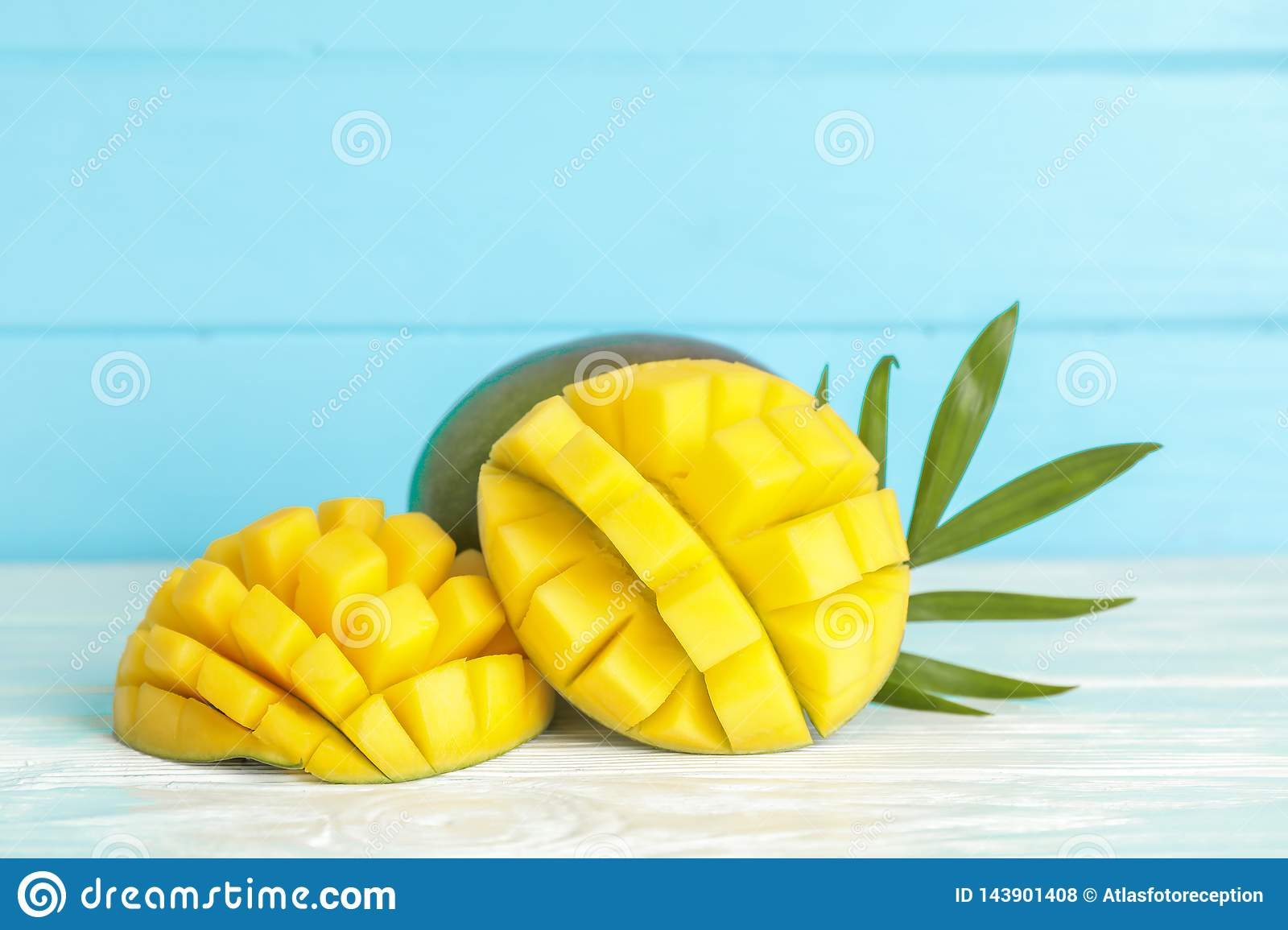 Cut ripe mangoes and palm leaf on white table against color background