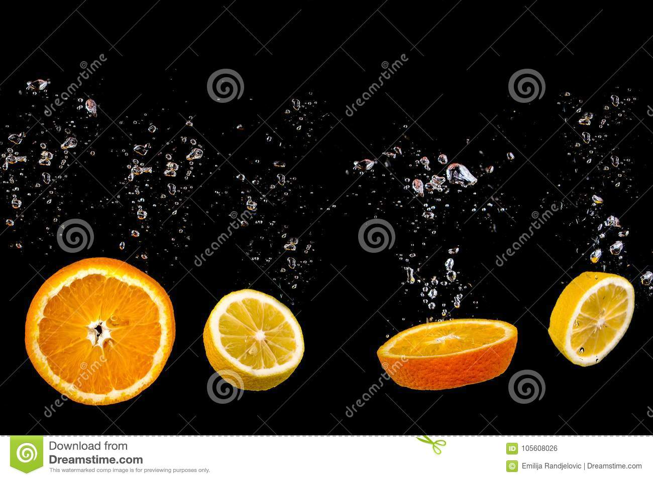 Cut Orange and lemon floats on water with bubbles, fruits is on a black background