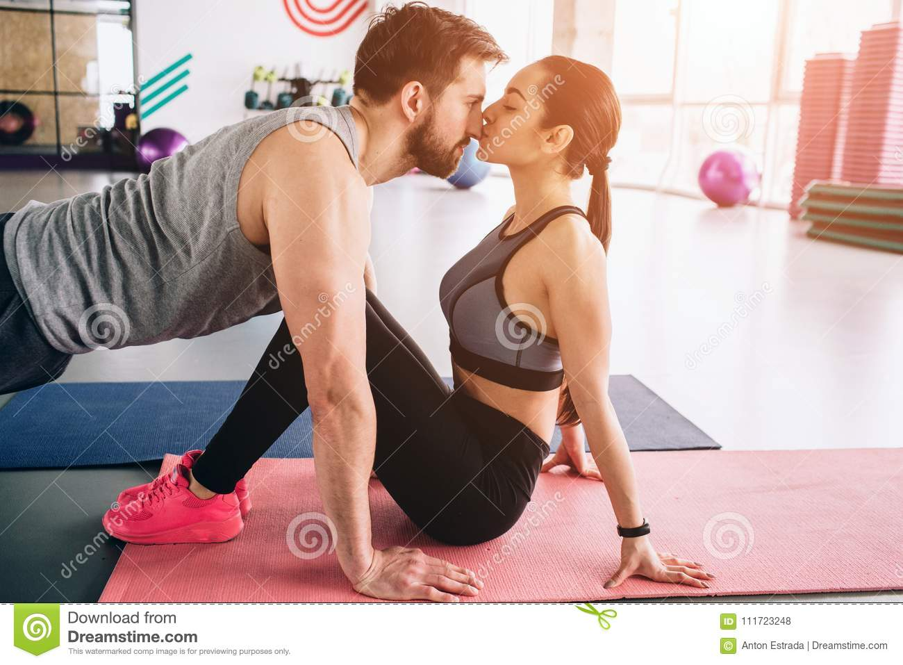 Cut view of a guy standing in a high plank position while his girlfriend is kissing him. It is so touchable and
