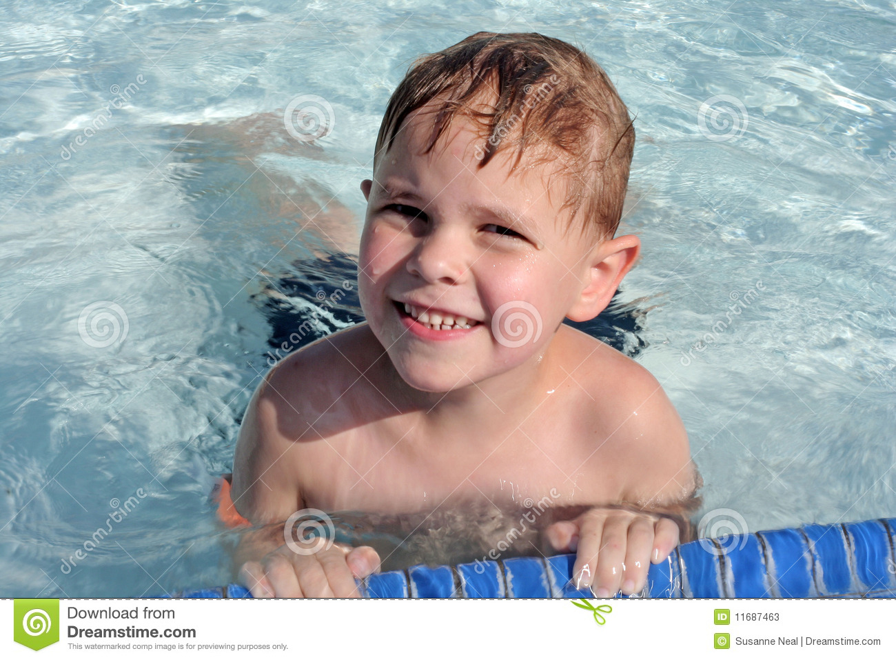 cute 6-year-old boy in swimming pool looking up at camera and