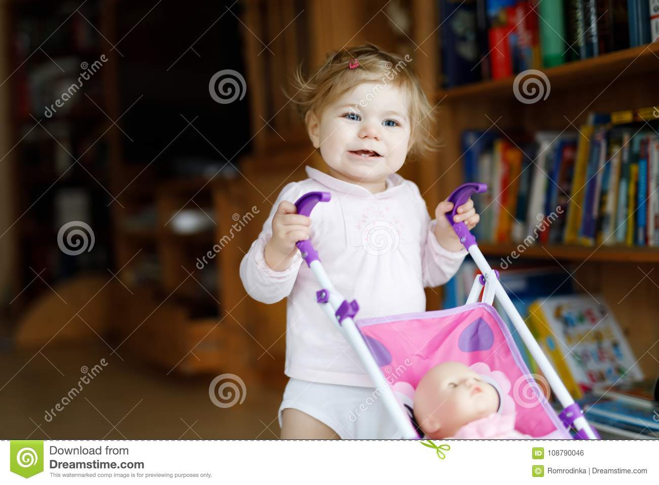 6a1b7422e Cute Adorable Baby Girl Making First Steps With Doll Carriage. Stock ...