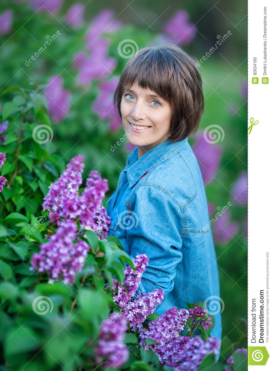 Cute adorable beautifull lady woman girl with brunette hair on a meadow of lilac purple bush.People in jeans wear.