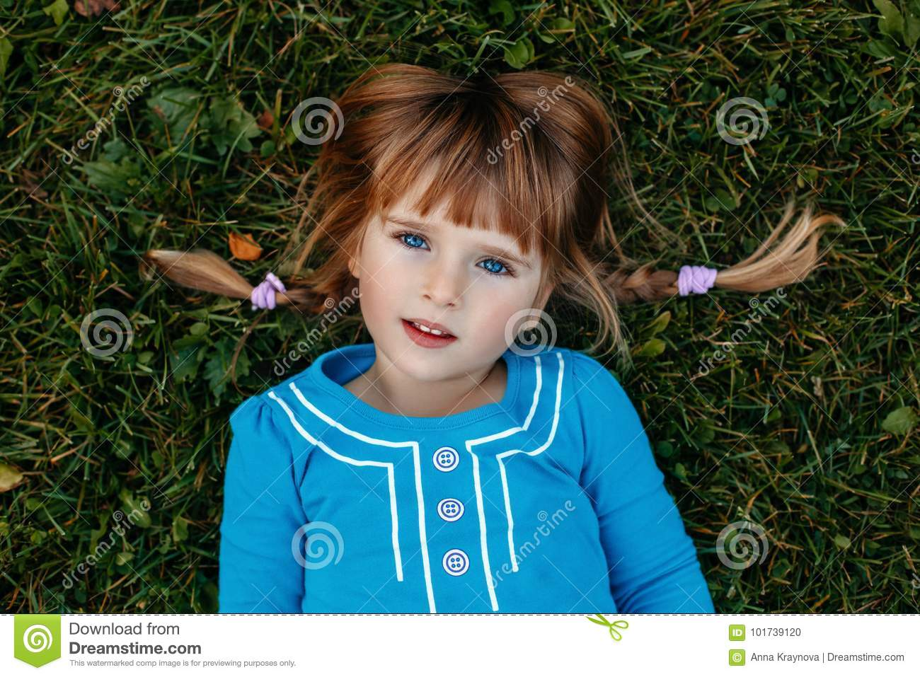 cute adorable little red-haired Caucasian girl child in blue dress lying in field meadow park outside