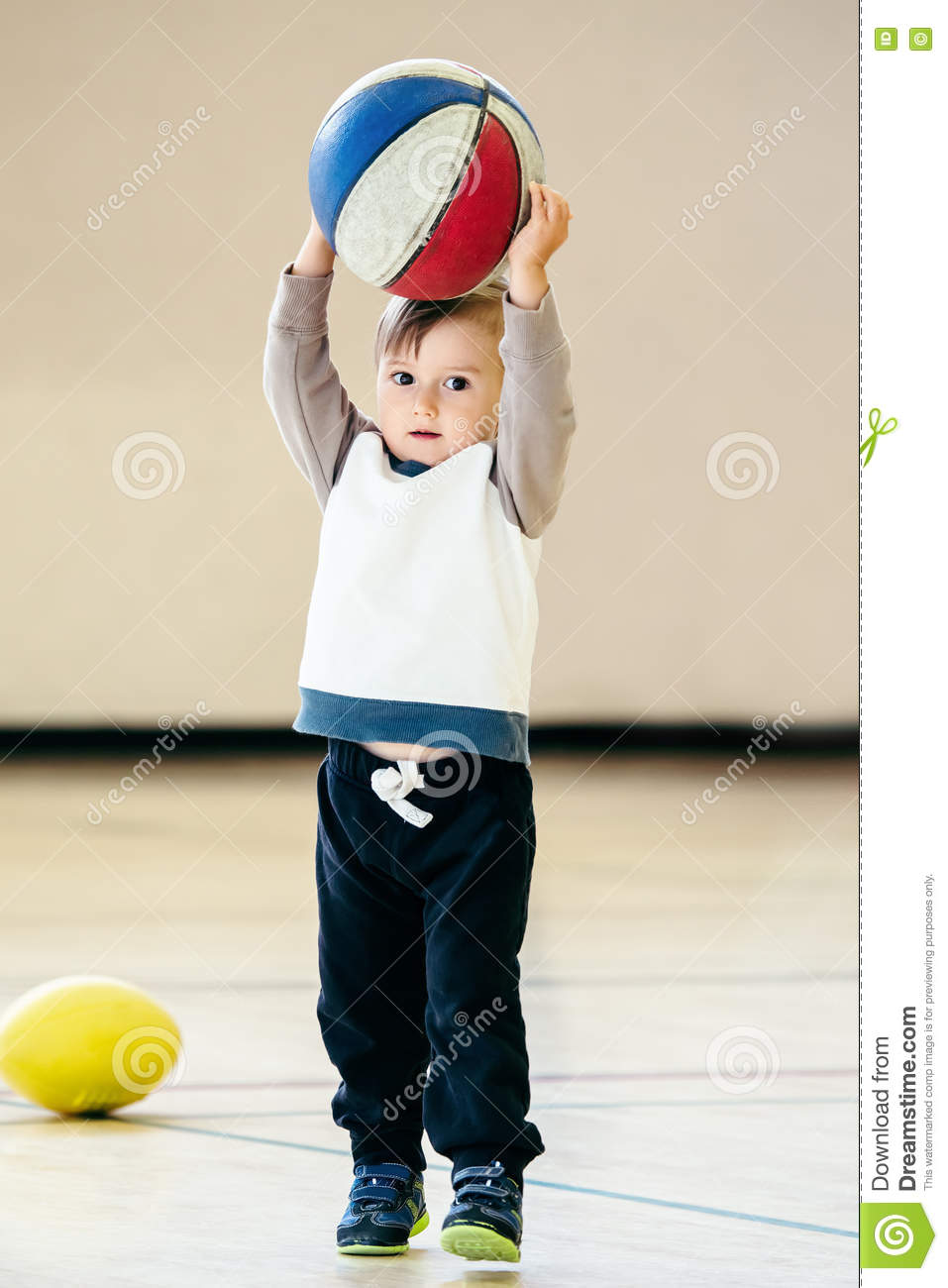 Cute adorable little small white Caucasian child toddler boy playing with ball basketball in gym on plain white light background