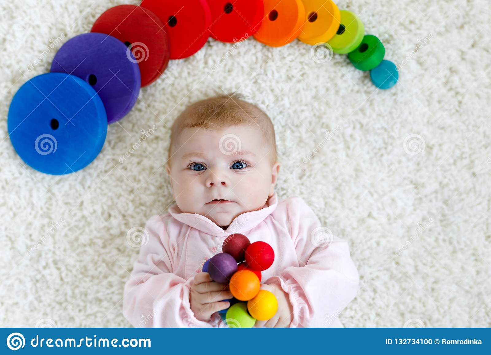 a13ebfd640f Cute adorable newborn baby playing with colorful wooden rattle toy ball on white  background. New