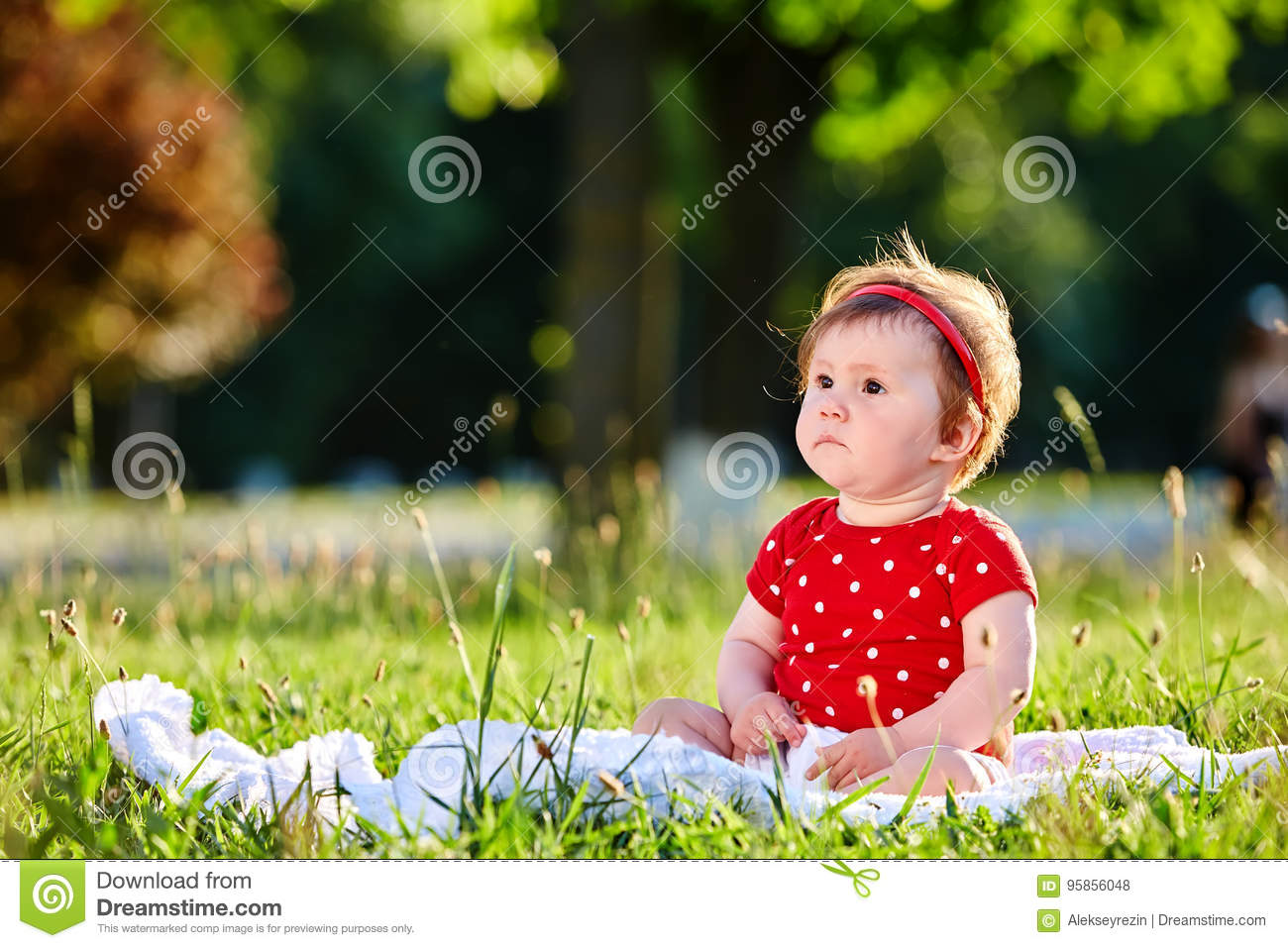 Cute adorable nice baby girl in red spring dress smiling sitting under the tree