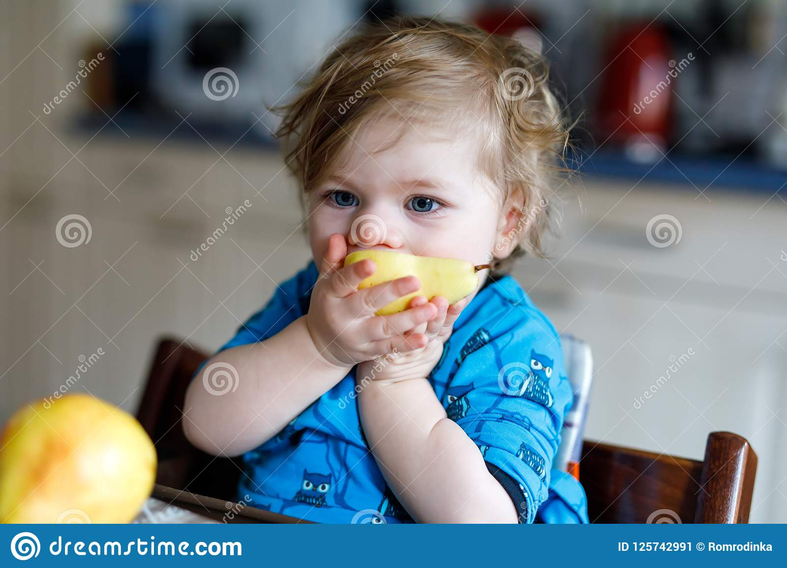 Cute adorable toddler girl eating fresh pear . Hungry happy baby child of one year holding fruit. Girl in domestic