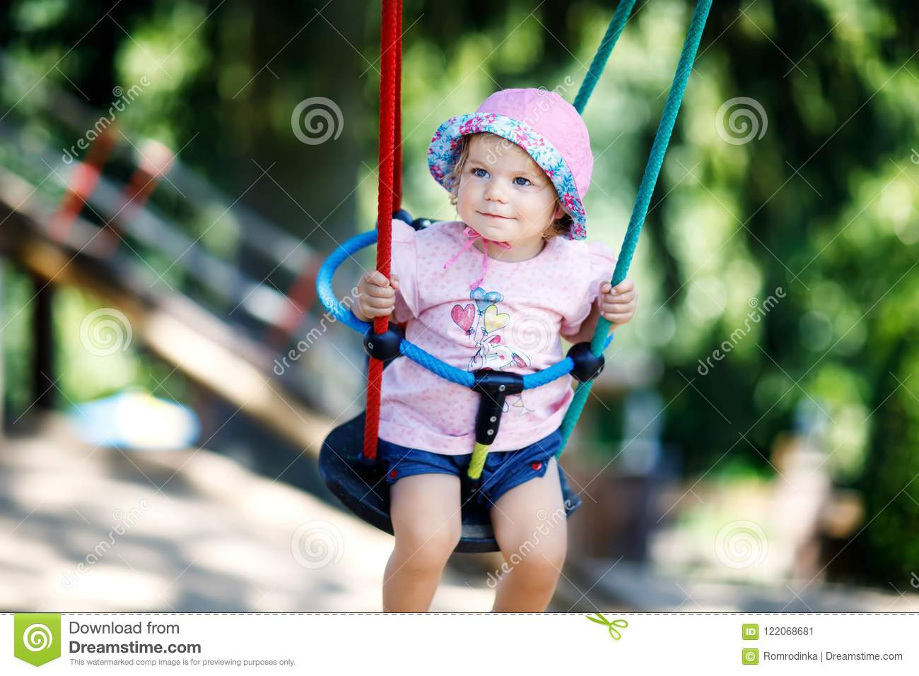 d40e9bbe4 Cute Adorable Toddler Girl Swinging On Outdoor Playground. Happy ...