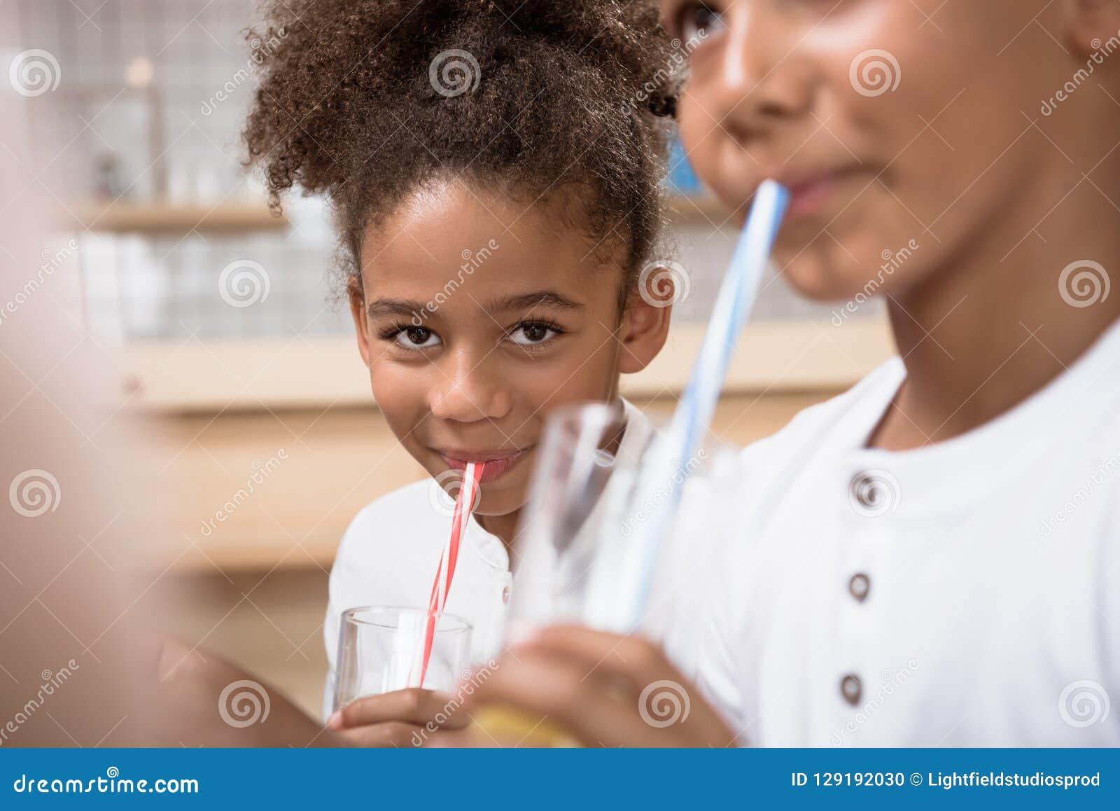 cute african-american kids drinking juice