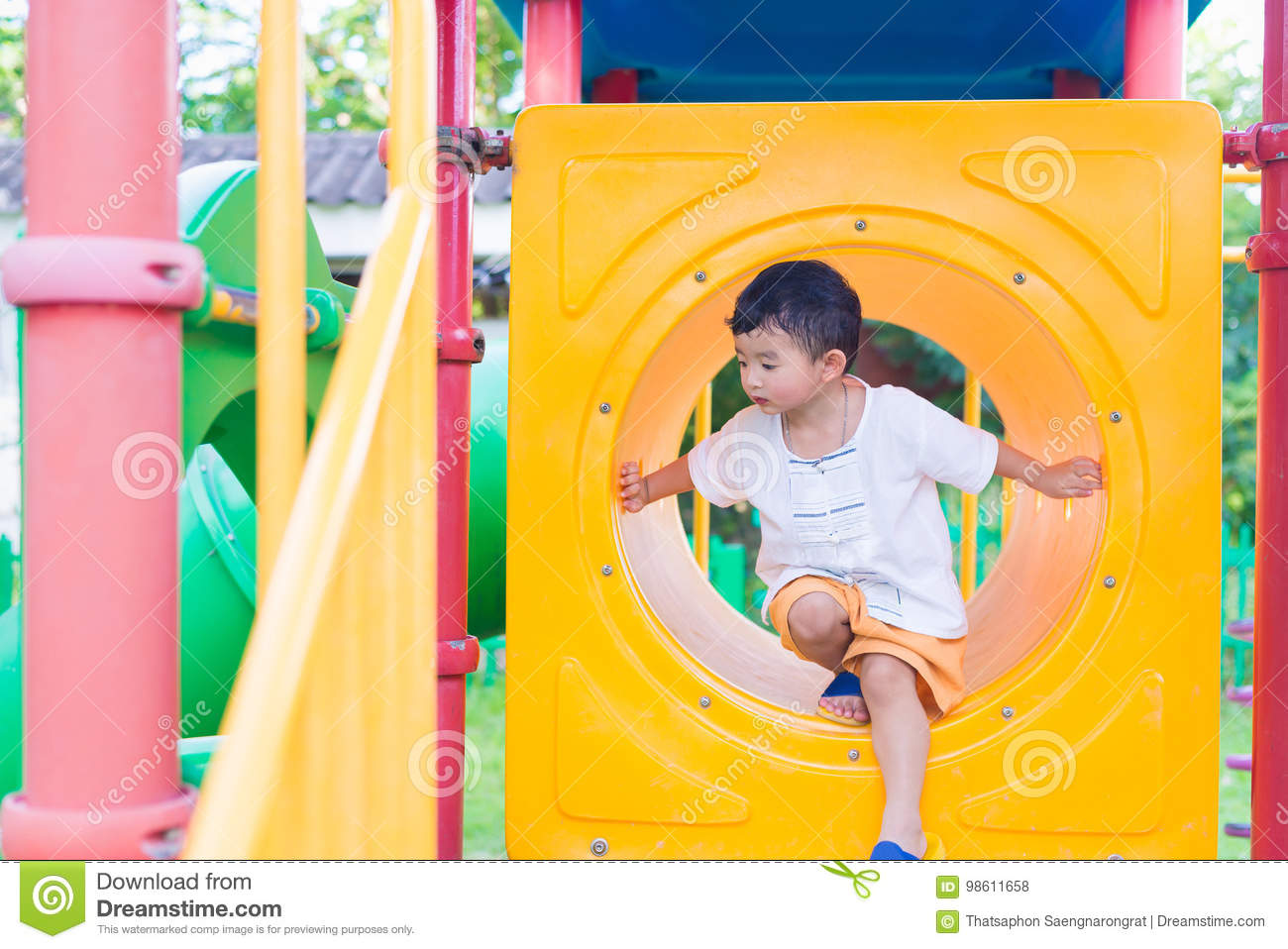 Cute Asian Boy Playing And Smiling In Yellow Tunnel At The Playground With Sunlight In Summer Yellow Tube Shallow Focus