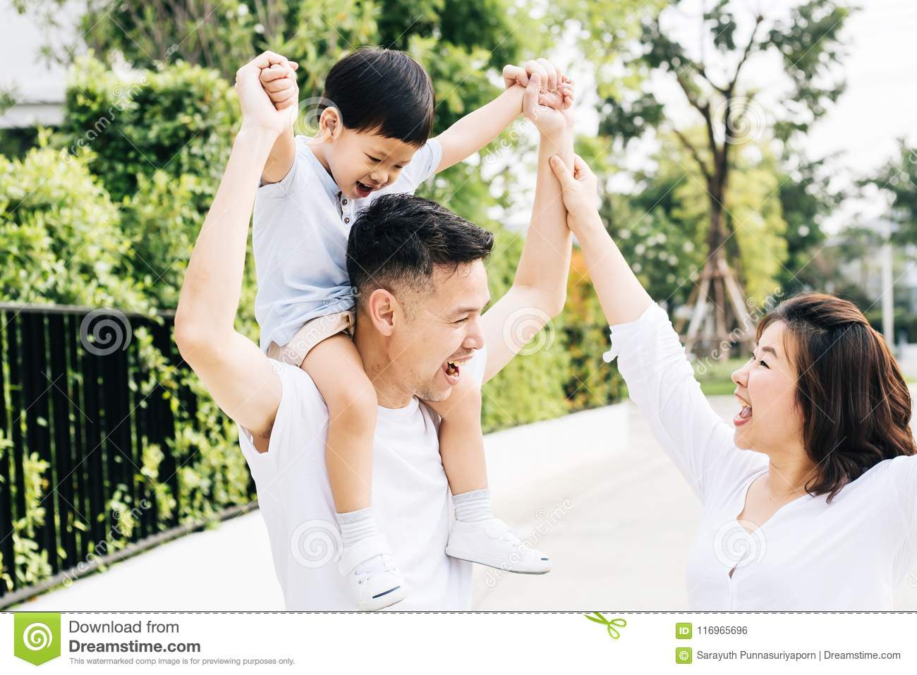 Cute Asian father piggybacking his son along with his wife in the park. Excited family raising hands together with happiness.