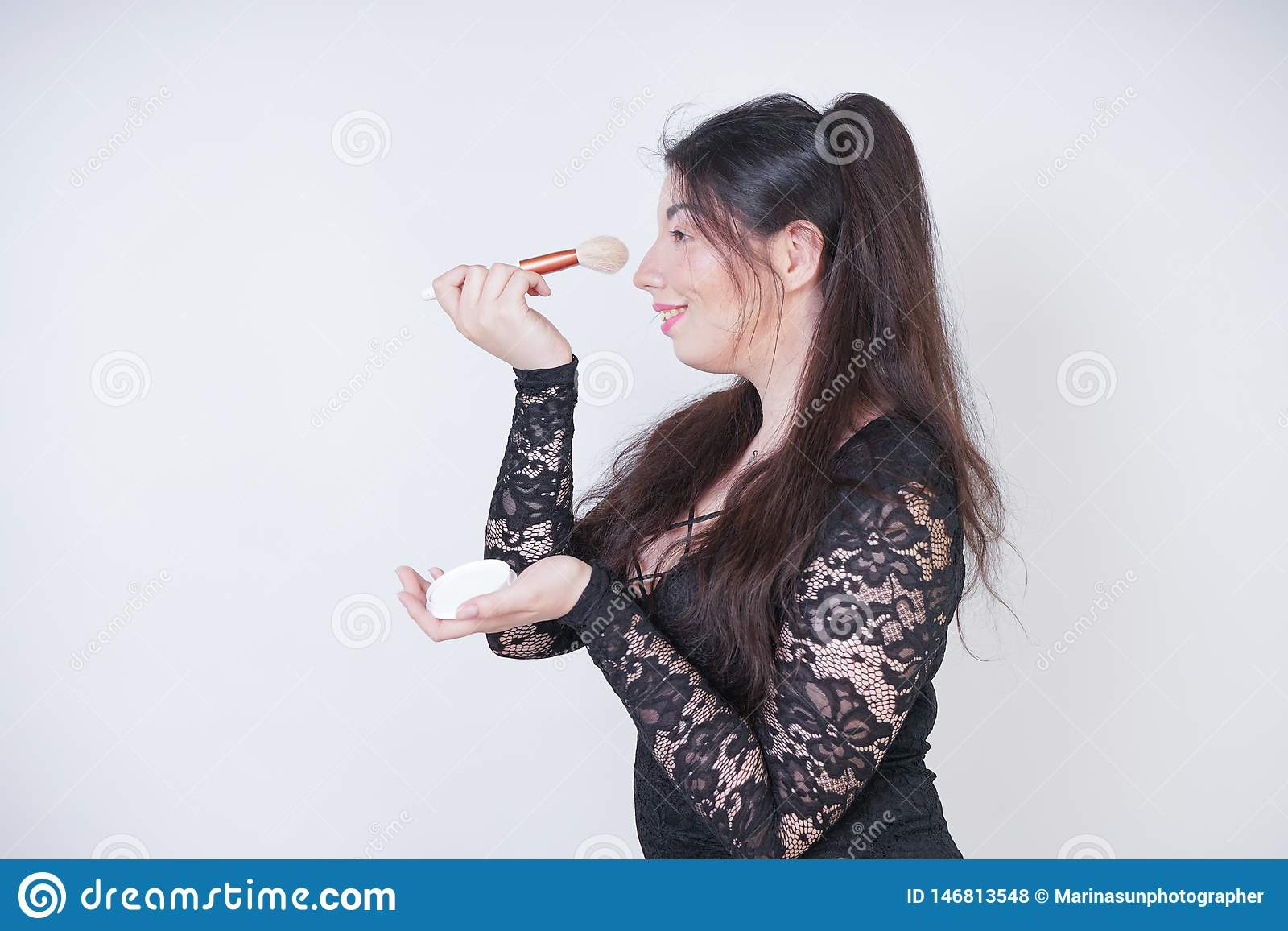 Cute Asian girl in black lace evening dress with powder and a brush in hands on white background