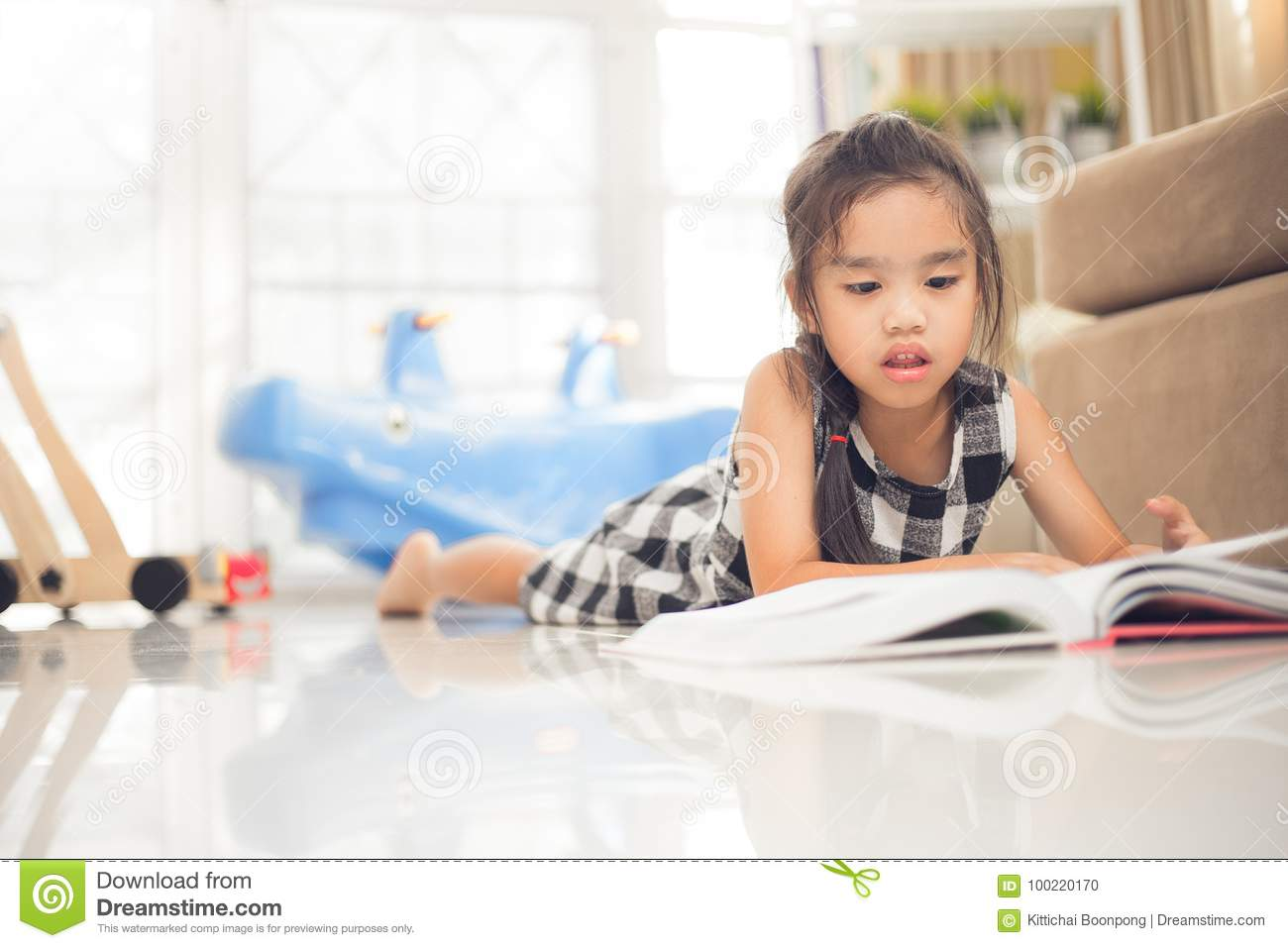 Cute Asian Girl Reading A Book While In The Live Room. Stock Photo ...
