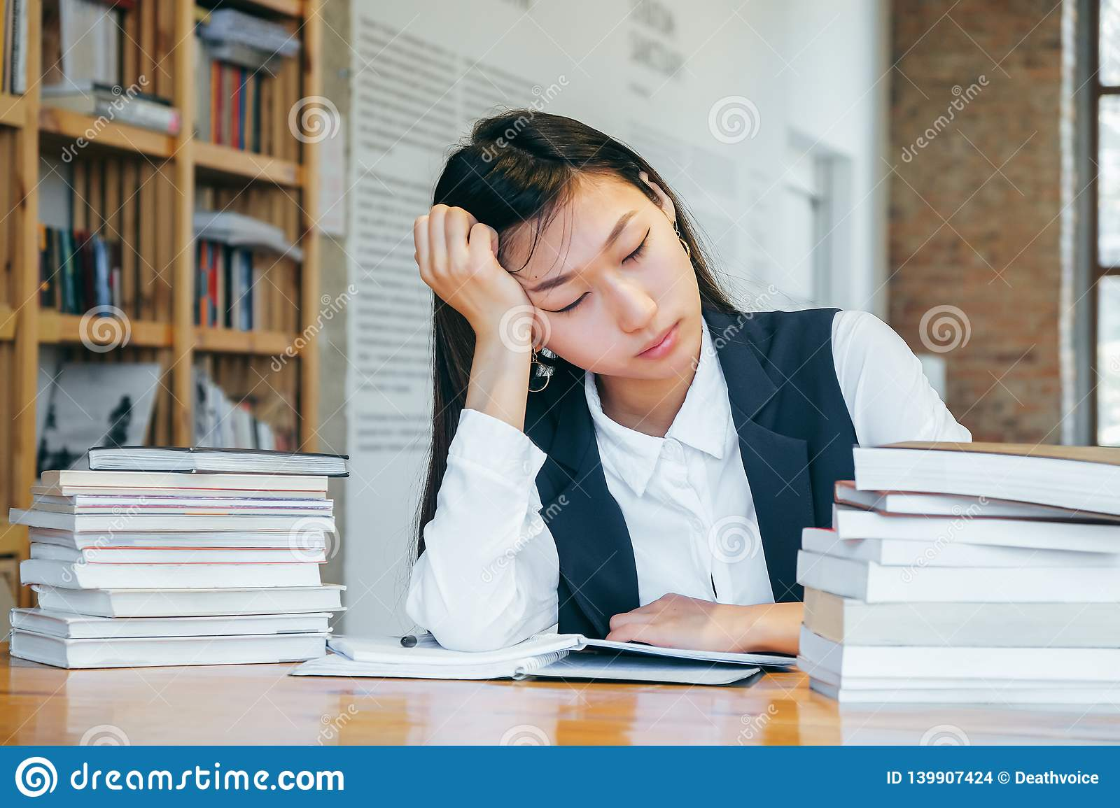 Cute Asian girl sitting in the library, surrounded by books, resting from school. A teenage student prepares for exams, takes
