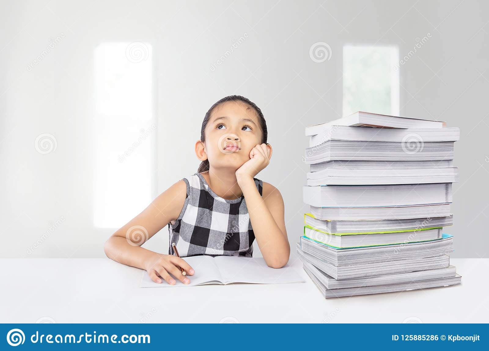 Cute asian girl tired on her study with huge stack of textbook on table
