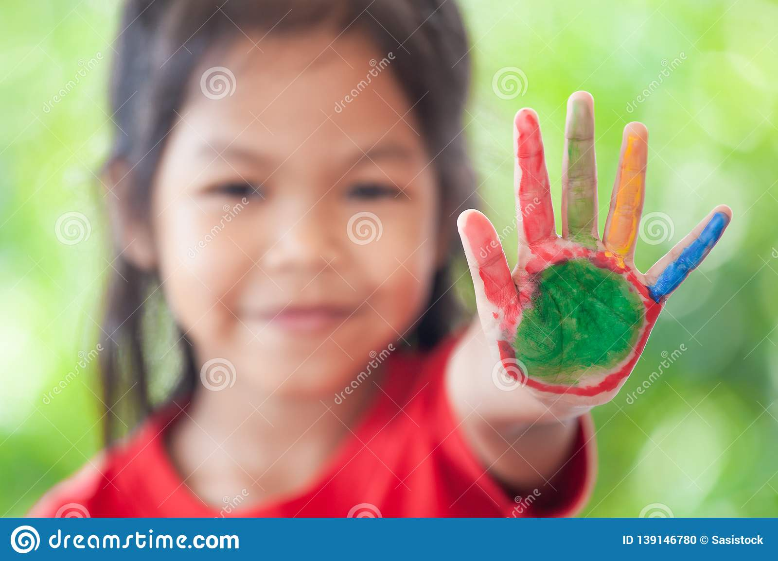 Asian little child girl with painted hands showing fingers number five