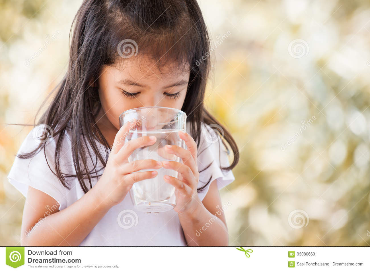 Cute asian little girl drinking fresh water from glass