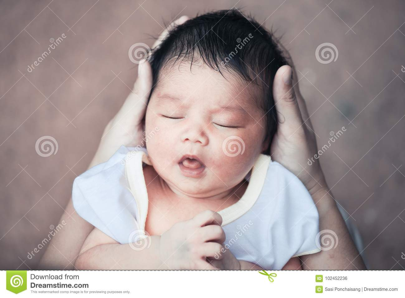 17d3b83c331 Cute asian newborn baby girl sleeping in mother hand. Mother holding head  of her baby in hands with tenderness in vintage color tone.