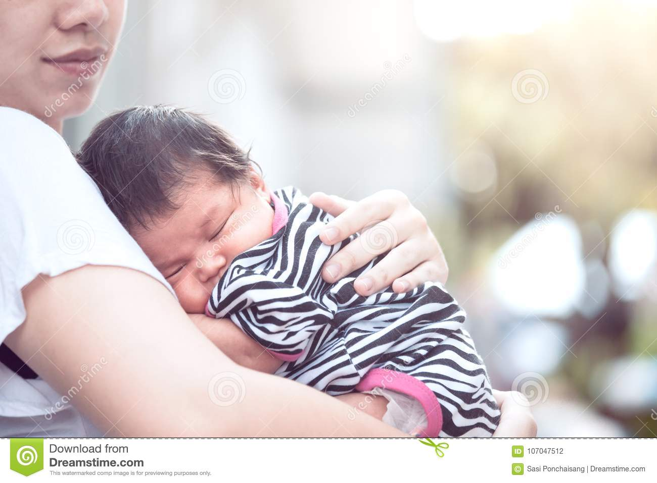 Cute asian newborn baby girl sleeping on mother`s chest.