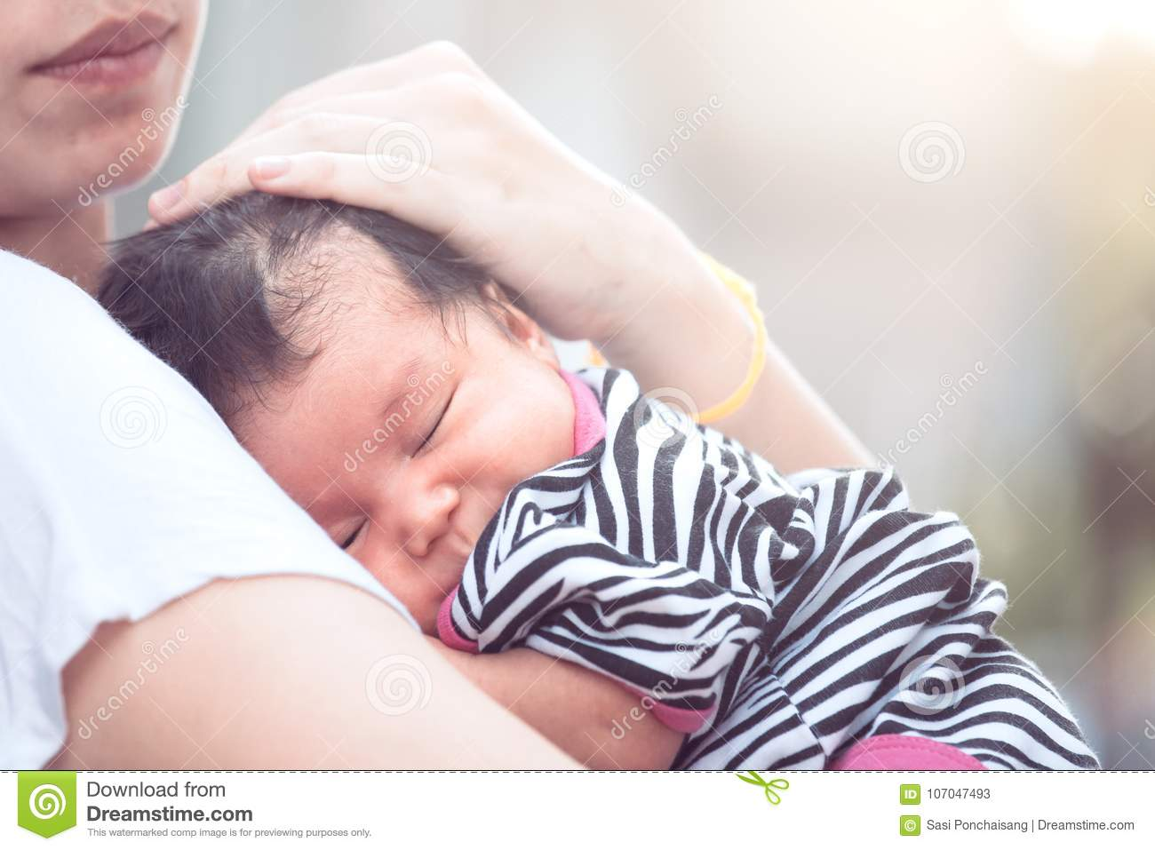 Cute asian newborn baby girl sleeping on mother`s chest