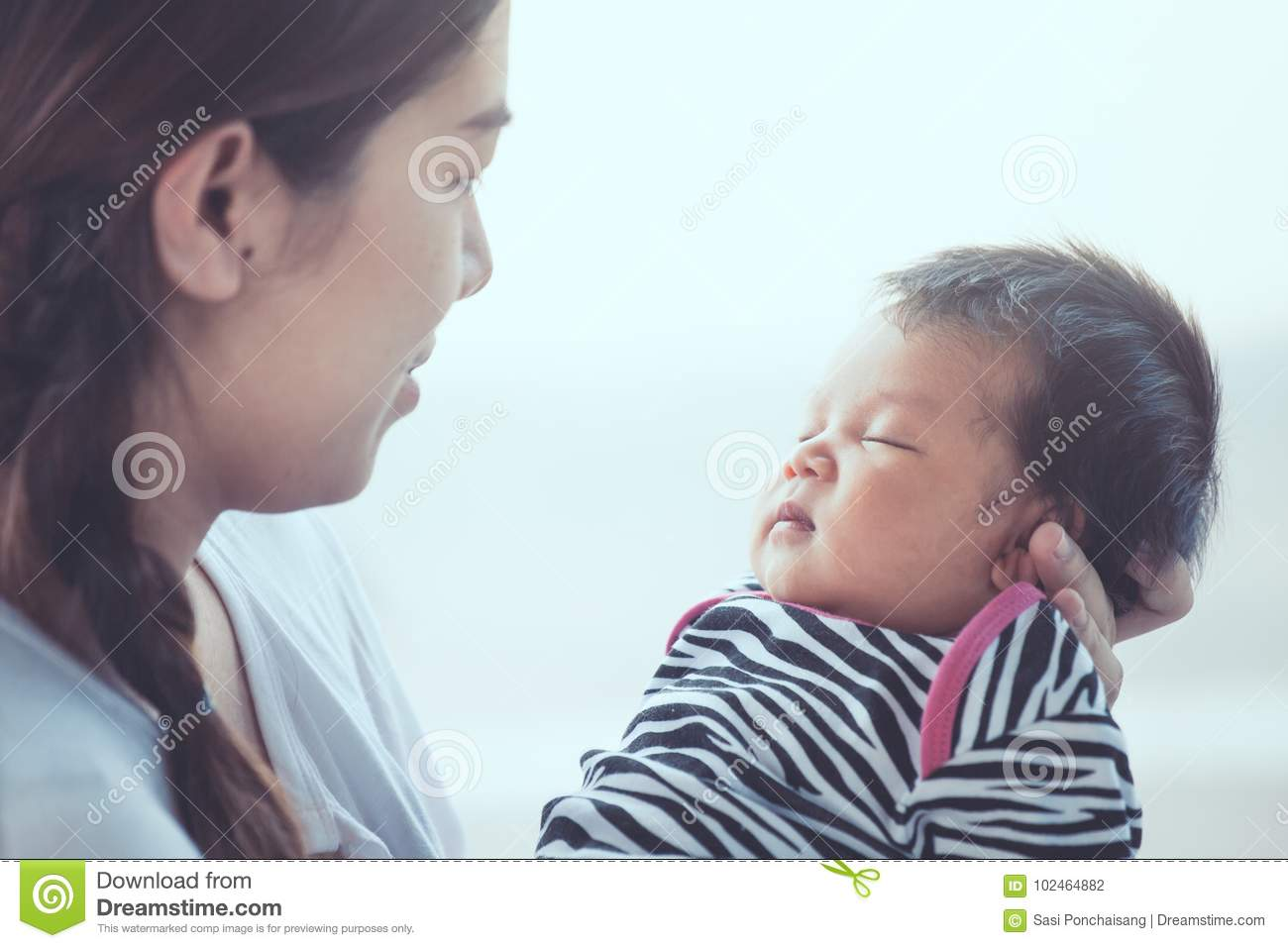 Cute asian newborn baby girl sleeping on mother`s hand.