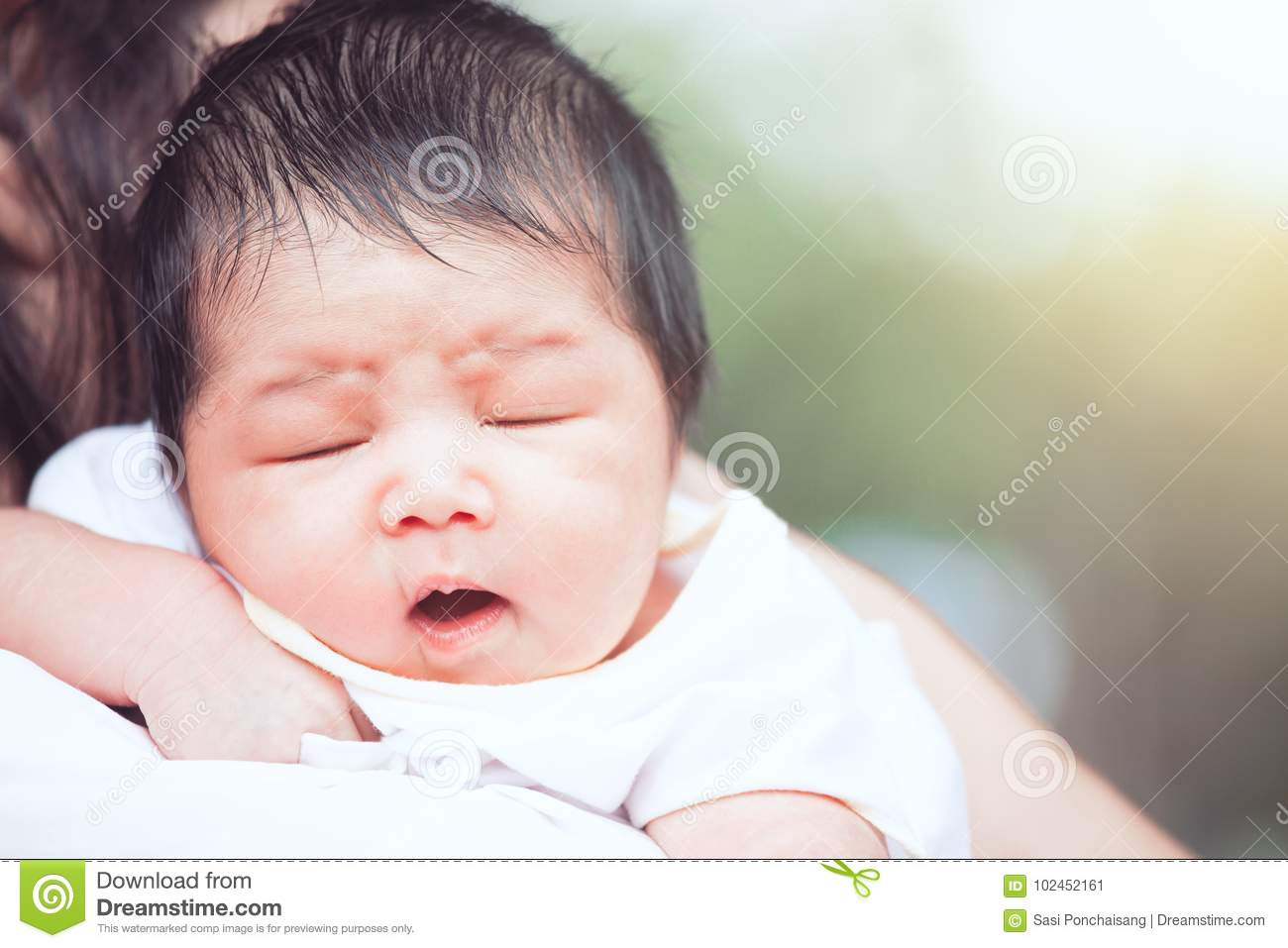 Cute asian newborn baby girl sleeping on mother`s shoulder