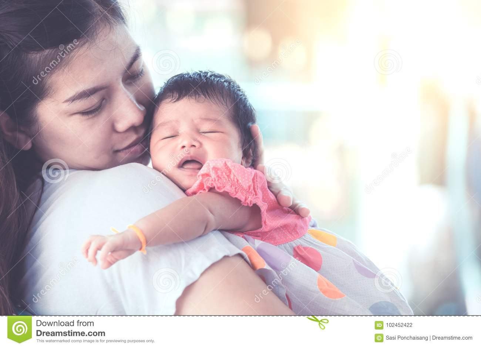Cute asian newborn baby girl sleeping on mother`s shoulder.