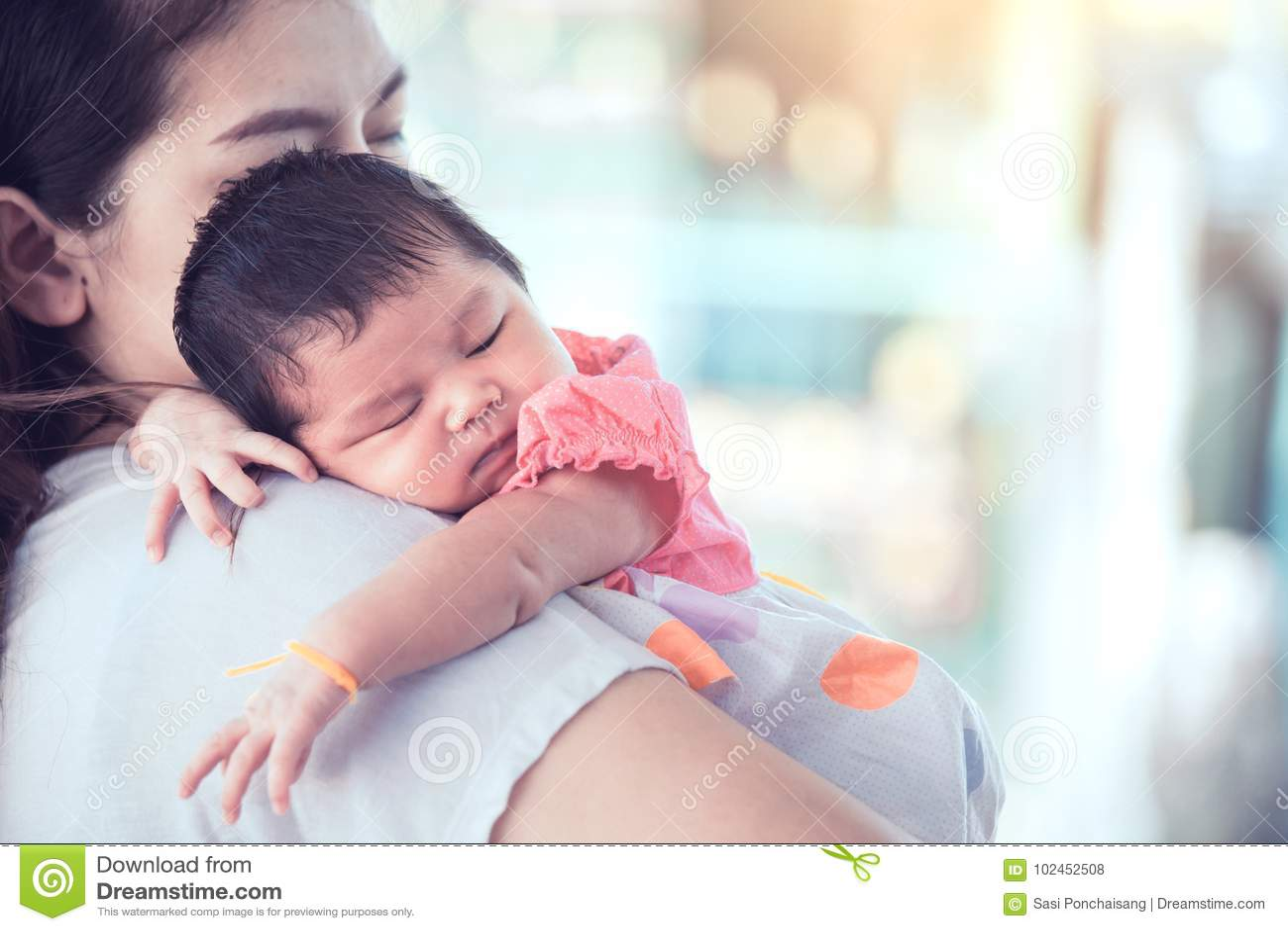 Cute asian newborn baby girl sleeping on mother`s shoulder