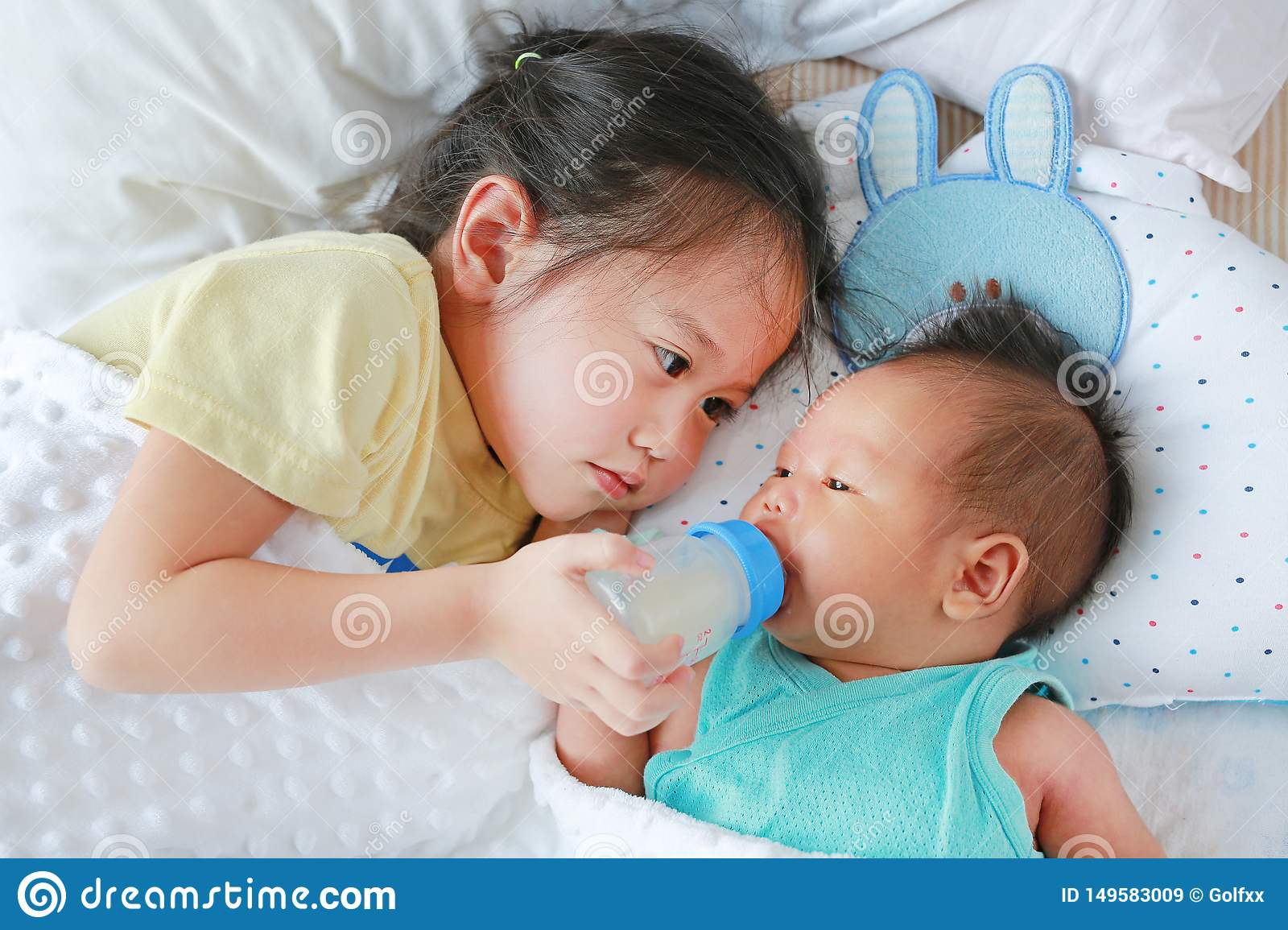Cute Asian Sister Feeding Milk From Bottle For Newborn ...