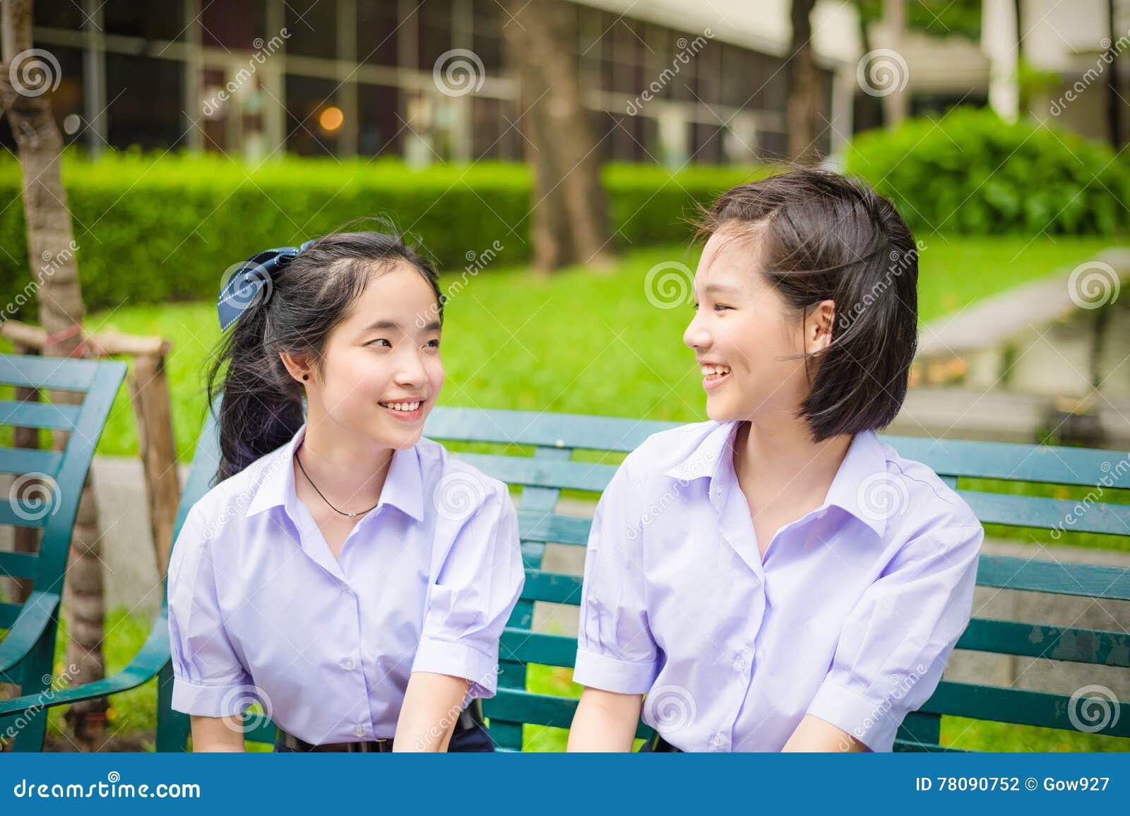 Cute Asian Thai high schoolgirls student couple chatting