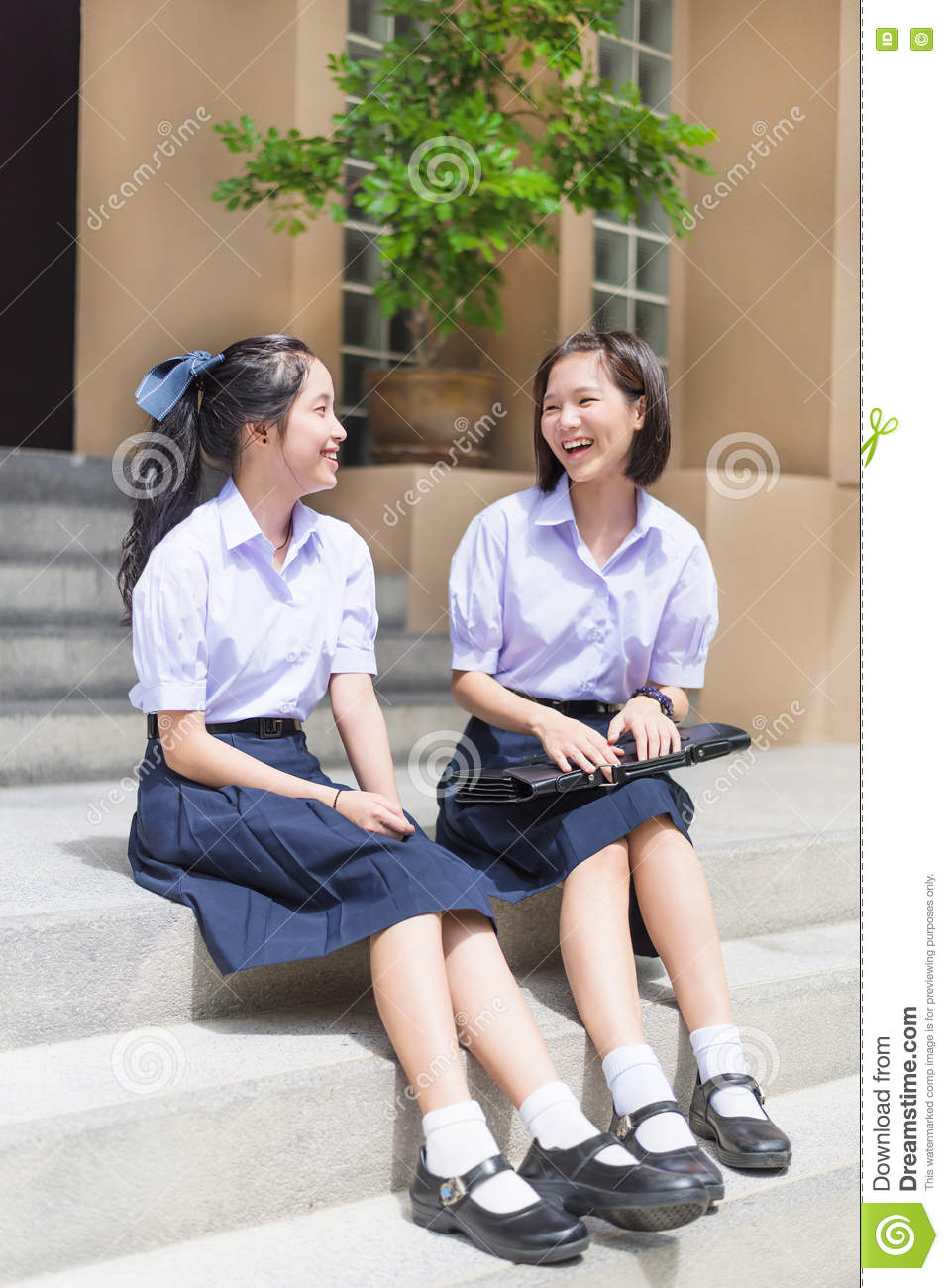 Cute Asian Thai high schoolgirls student couple happy chatting