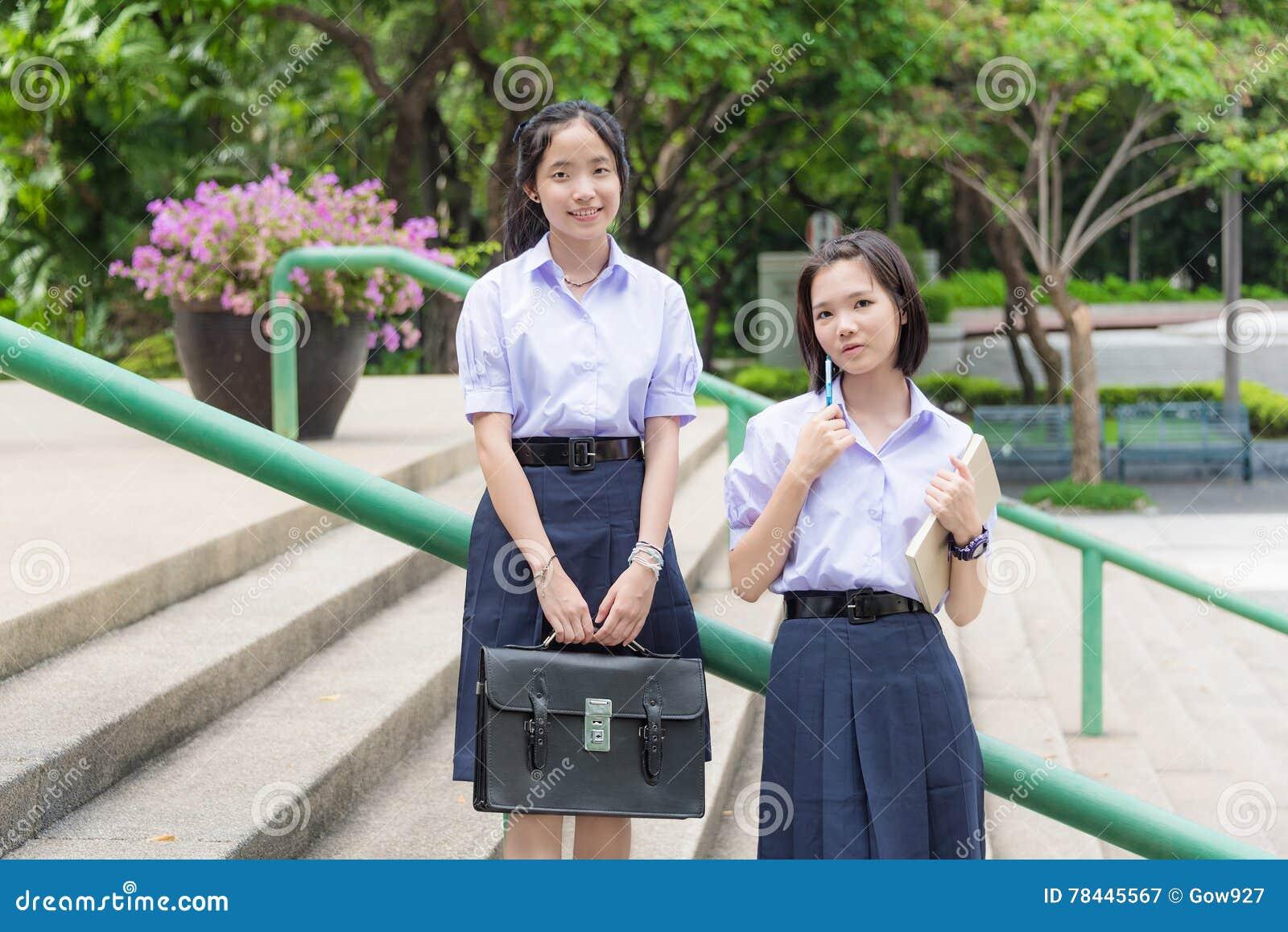 Cute Asian Thai high schoolgirls student couple in school uniform